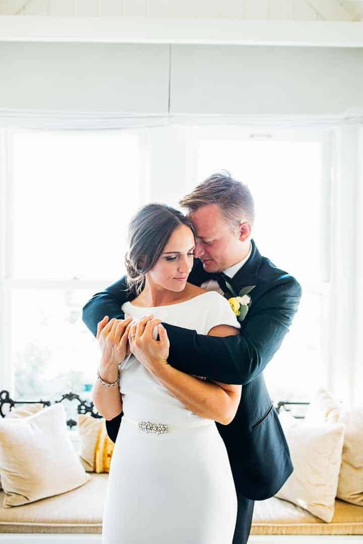 Groom-Wraps-Arms-Around-Bride-Bright-Room-Utah