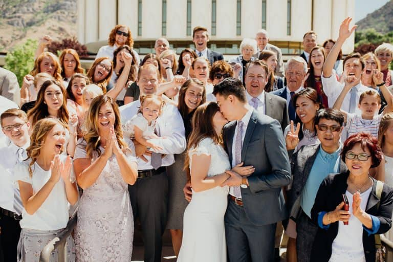 Newlyweds kissing outside of gorgeous temple