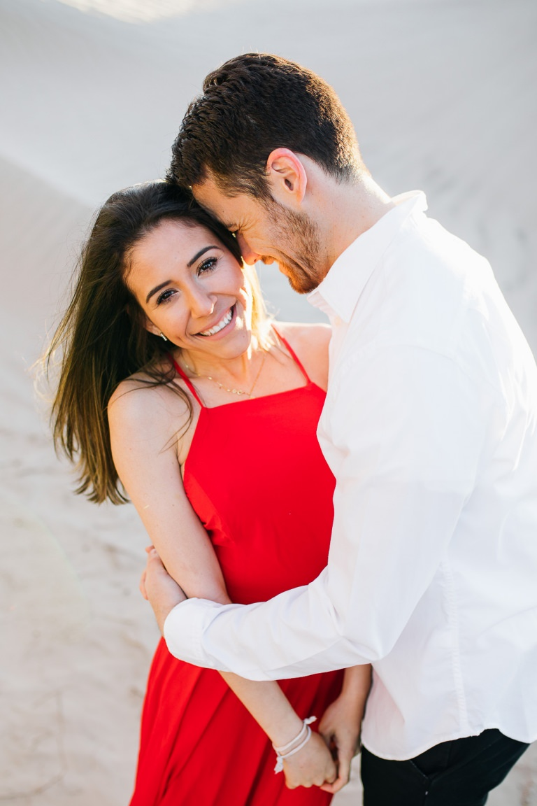 Smiling red dress engagement photo