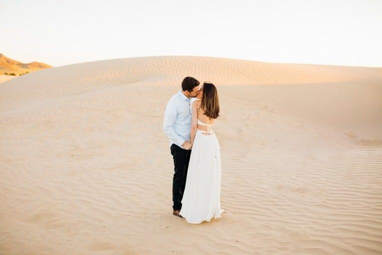 Golden hour kissing in white flow dress