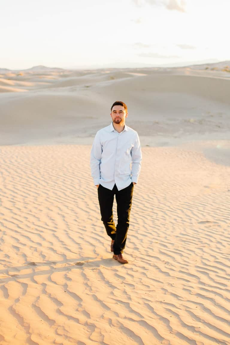 Handsome fiancé walking in the sand