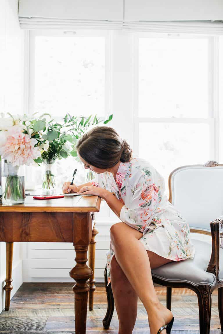 Bride writing down vows for wedding day morning