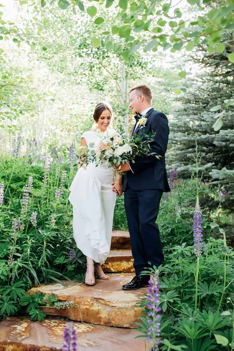 Bride and groom walking through green nature
