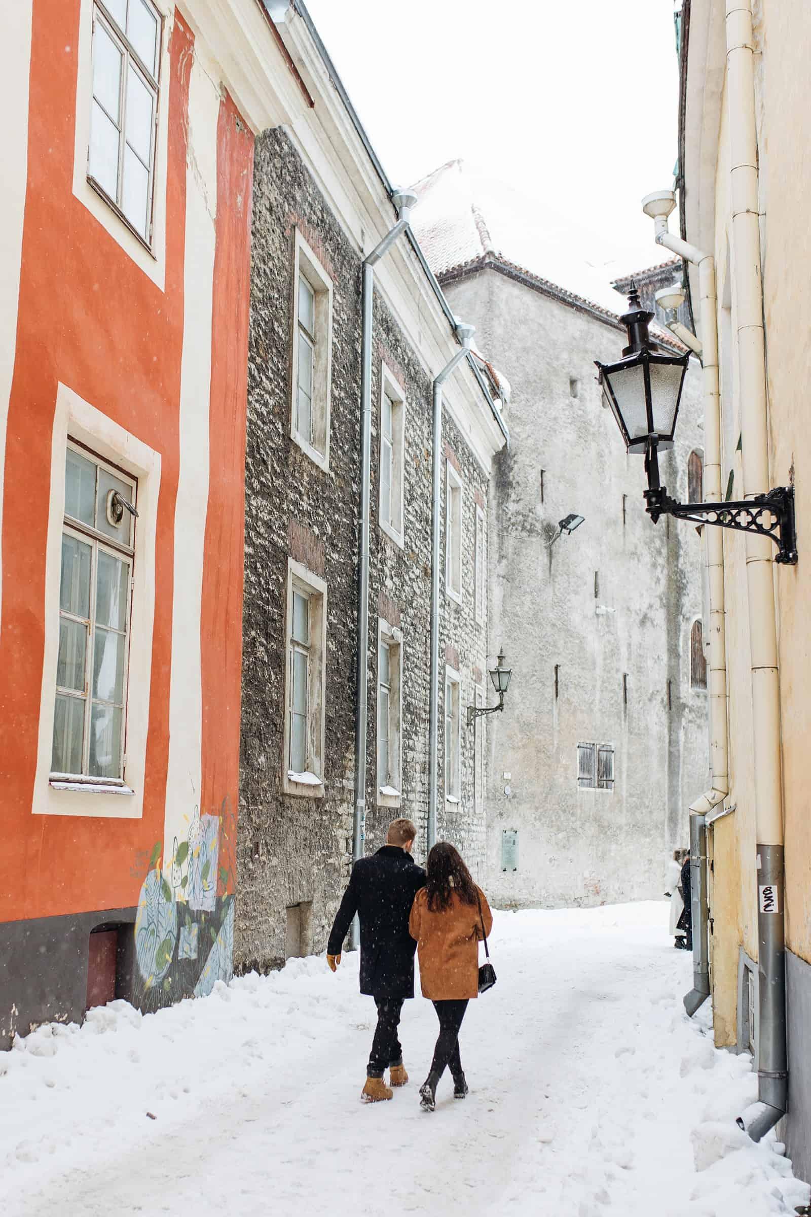 couple walking through snowing Estonia European town