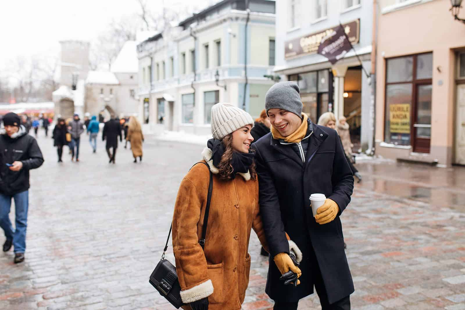 couple walking through estonia with coffee, engagement pictures, European city, travel photography