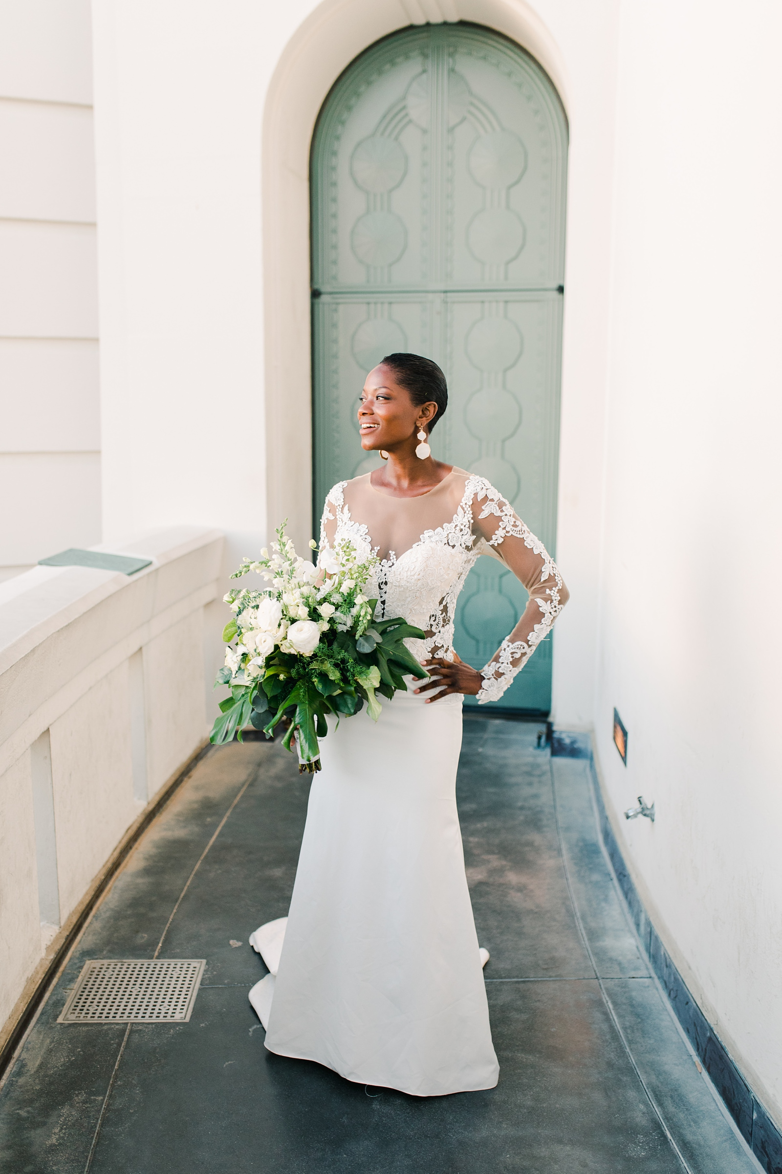 Modern timeless wedding photography at the Griffith Observatory in Los Angeles, California destination wedding photographer, modern bride with long sleeve lace dress, short hair and white flowers with tropical greenery