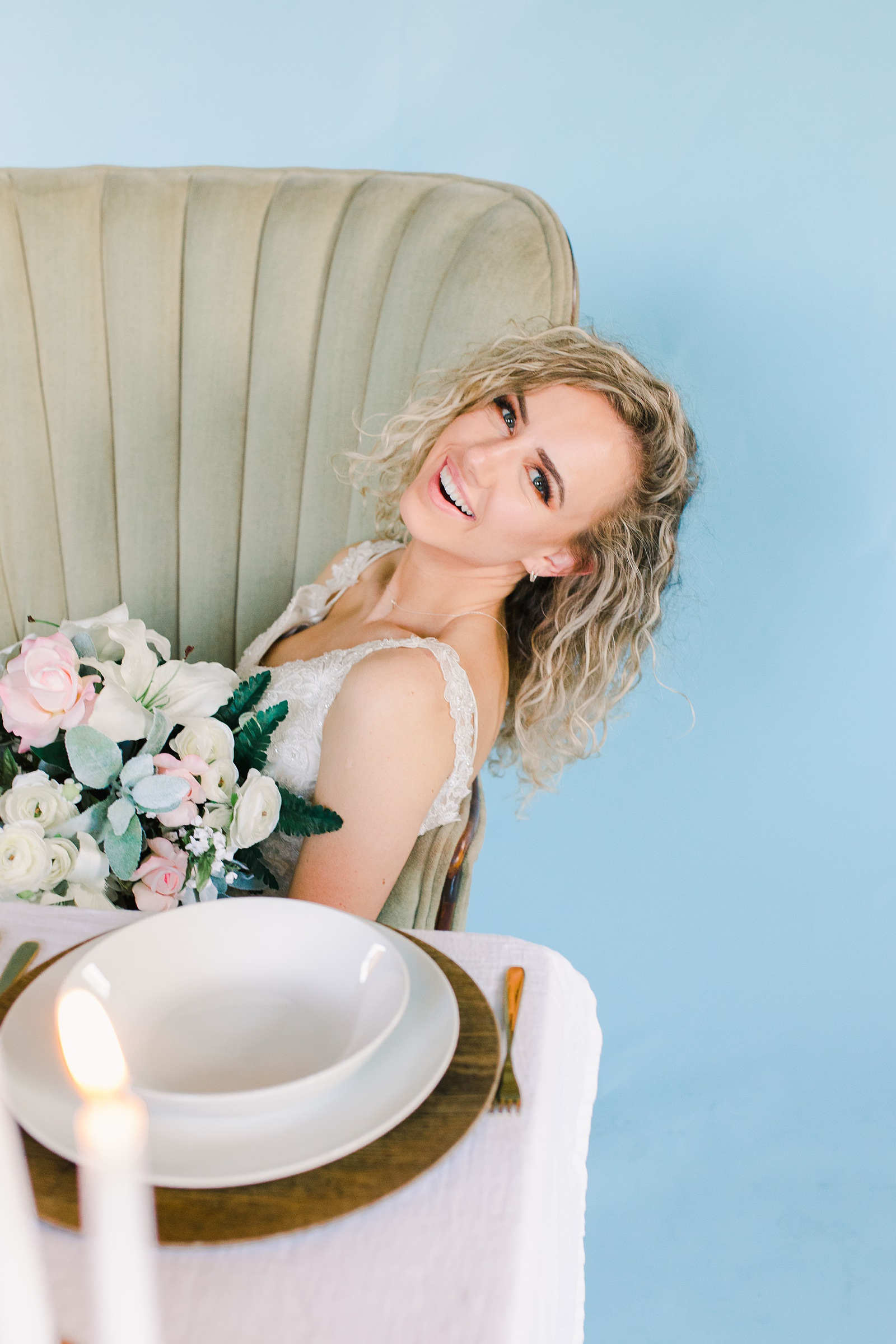 Utah wedding photography, bride with lace wedding dress and sweetheart table with greenery garland with eucalyptus and white flowers and blue wall