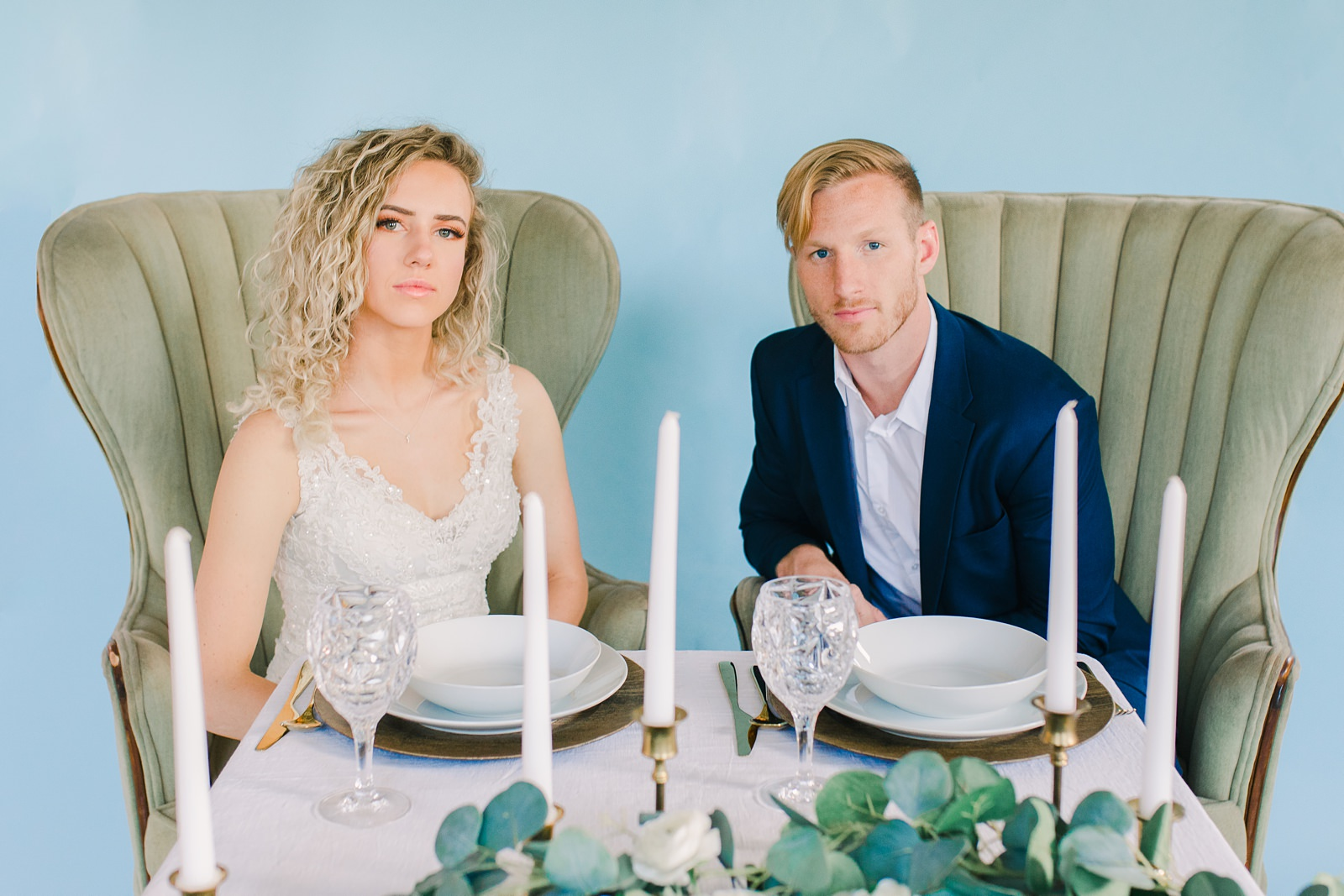 Utah wedding photography, bride and groom at sweetheart table with greenery garland with eucalyptus and white flowers and blue wall