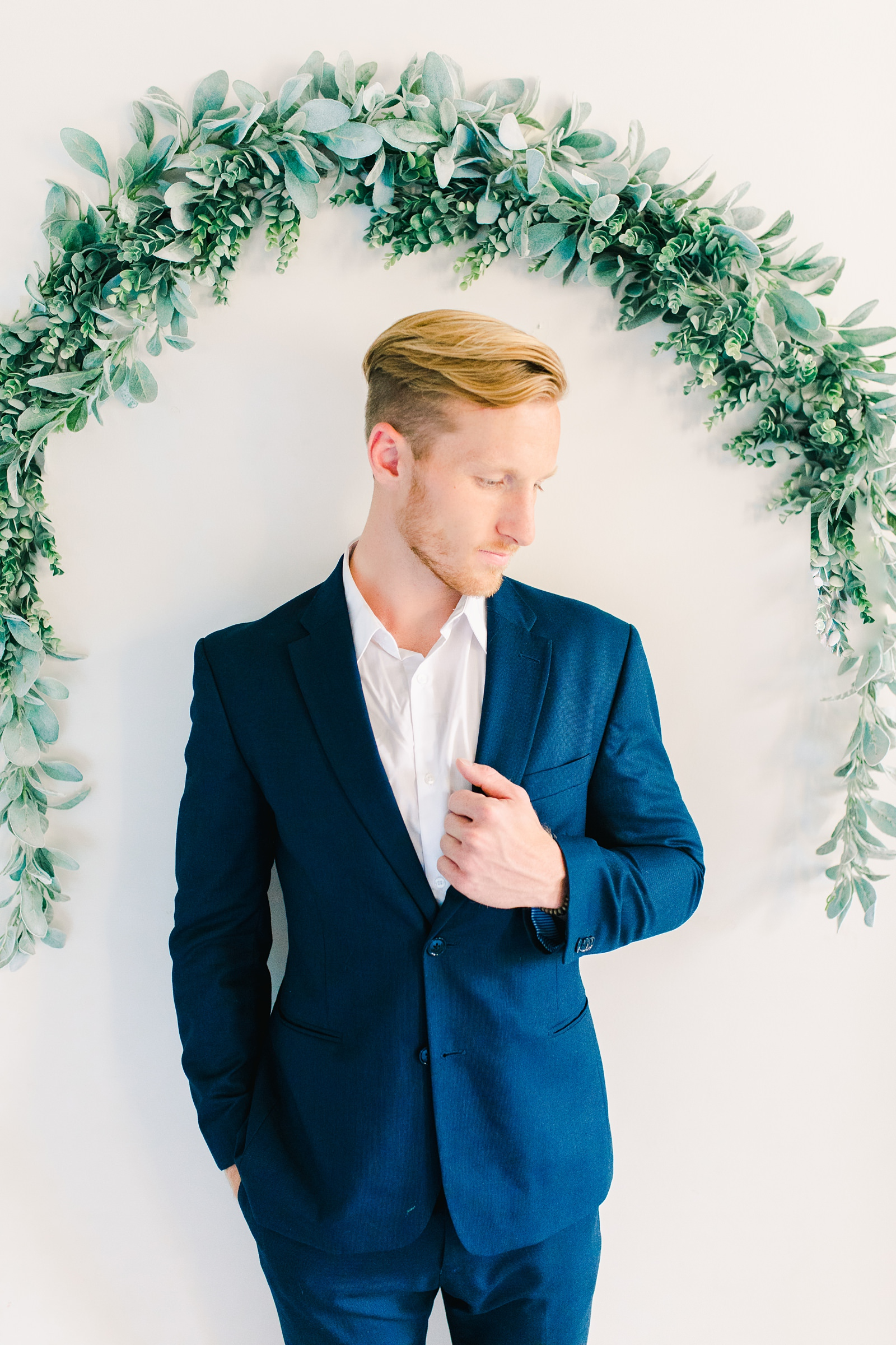 Utah wedding photography, groom in navy blue suit and white tie in front of white wall with eucalyptus greenery garland arch