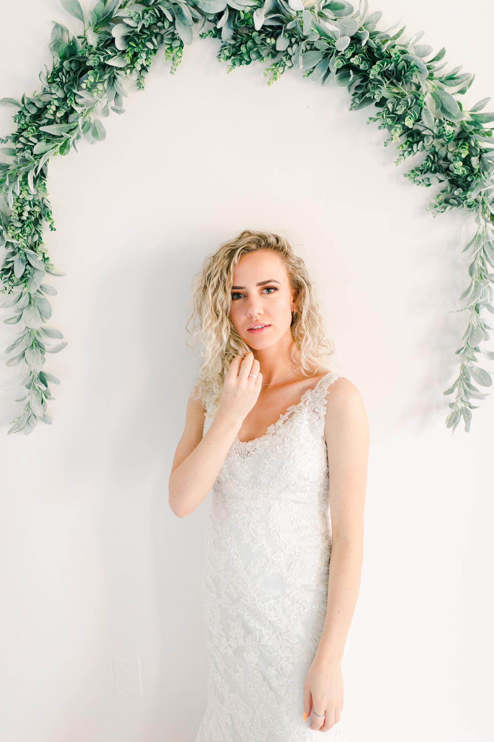 Utah wedding photography, bride in lace wedding dress with long flowy veil and white tie in front of white wall with eucalyptus greenery garland arch