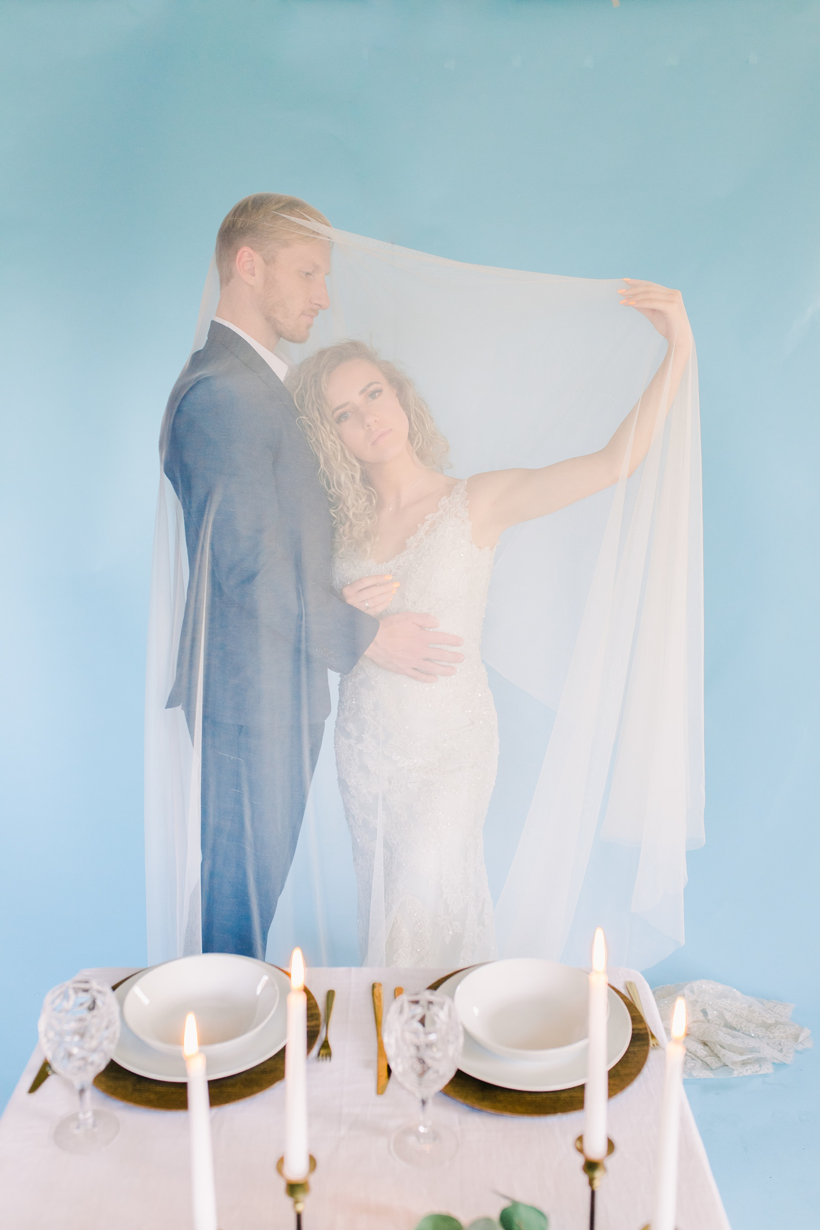 Utah wedding photography, bride and groom with long flowy draped veil in front of blue wall