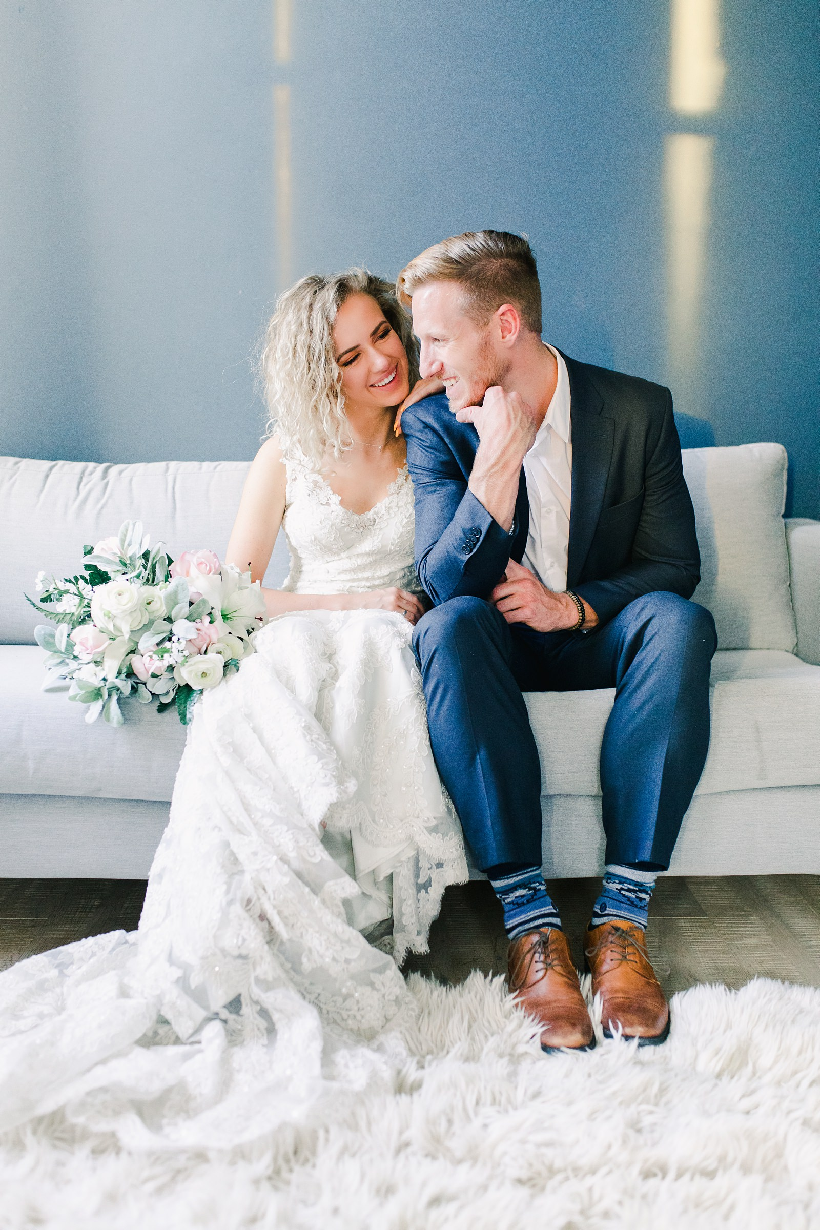 Utah wedding photography, bride and groom relaxed pose on couch in front of blue wall, white flowers wedding bouquet with greenery
