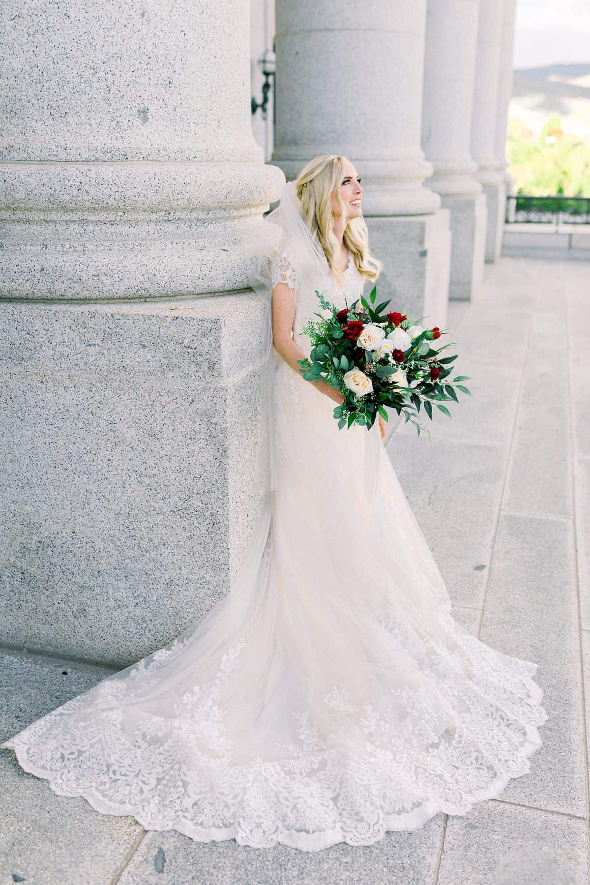 Modest lace wedding dress, bride with long veil and long hairstyle, red and white wedding flowers bouquet
