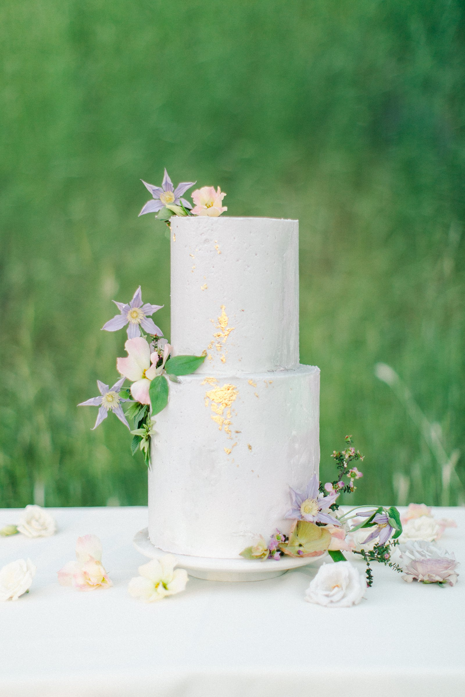 French pastel wedding , white and lavender two tier buttercream wedding cake with edible gold leaf and purple flowers, fine art film wedding photography
