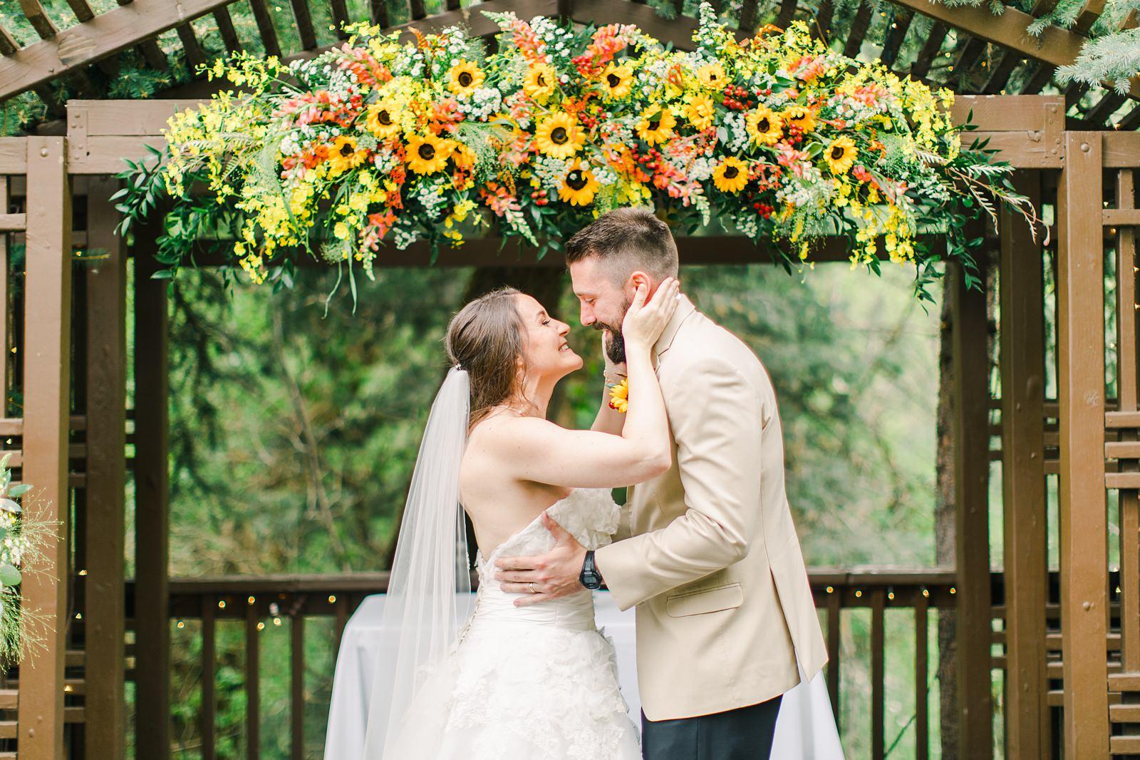 Millcreek Inn Summer Wedding, Utah wedding photography Millcreek Canyon, Salt Lake City, bride and groom kiss under sunflower wildflower arch wedding flowers decor