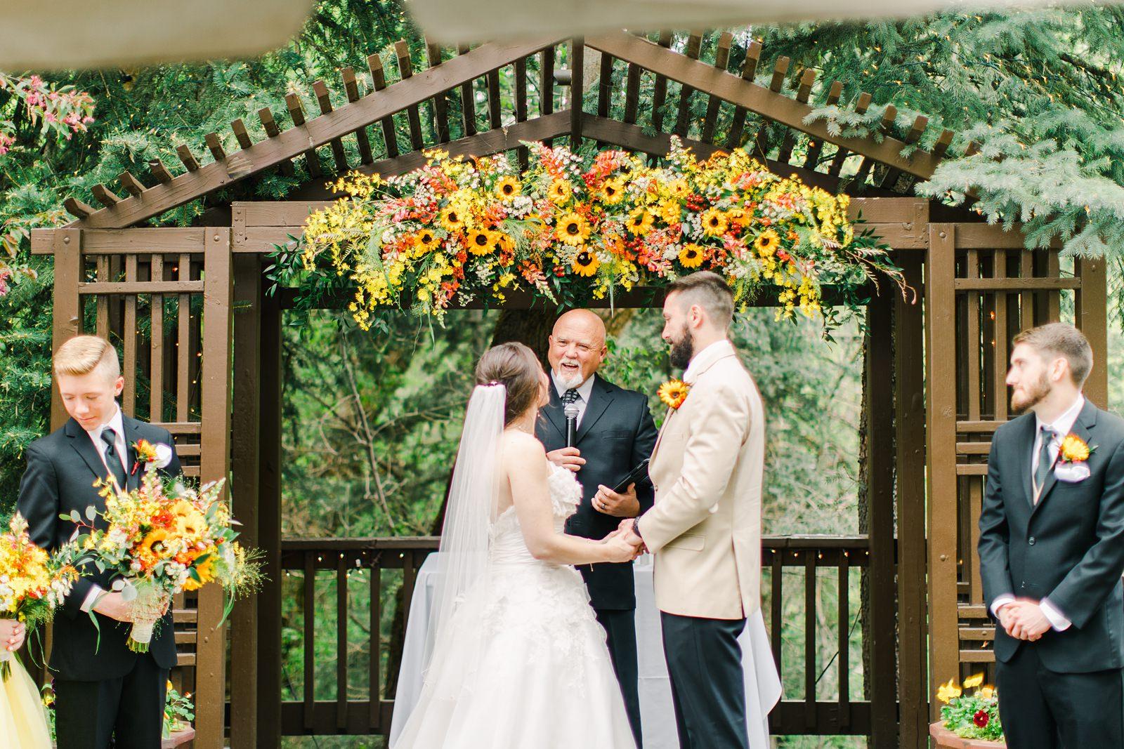 Millcreek Inn Summer Wedding, Utah wedding photography Millcreek Canyon, Salt Lake City, mountain ceremony, bride and groom under sunflower wildflower arch