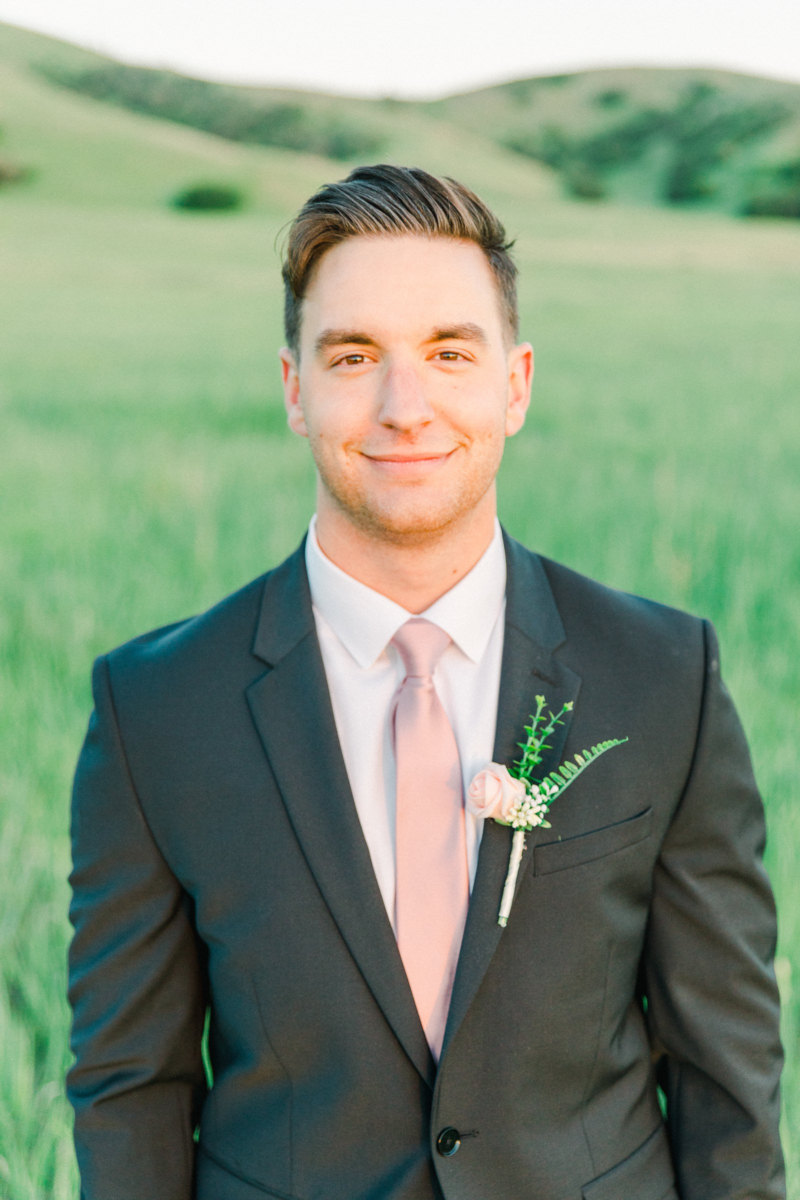 Salt Lake City Utah Bridal Wedding Photography, Tunnel Springs Park, groom in dark gray suit and pink tie, open green field