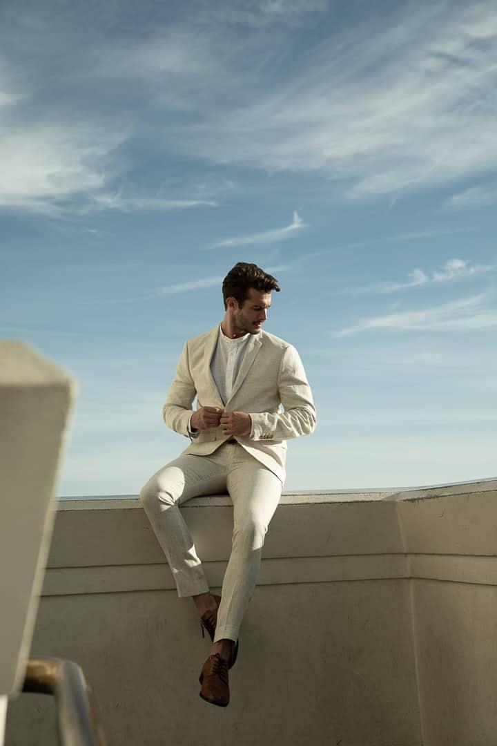 groom-on-wall-wedding-blue-sky