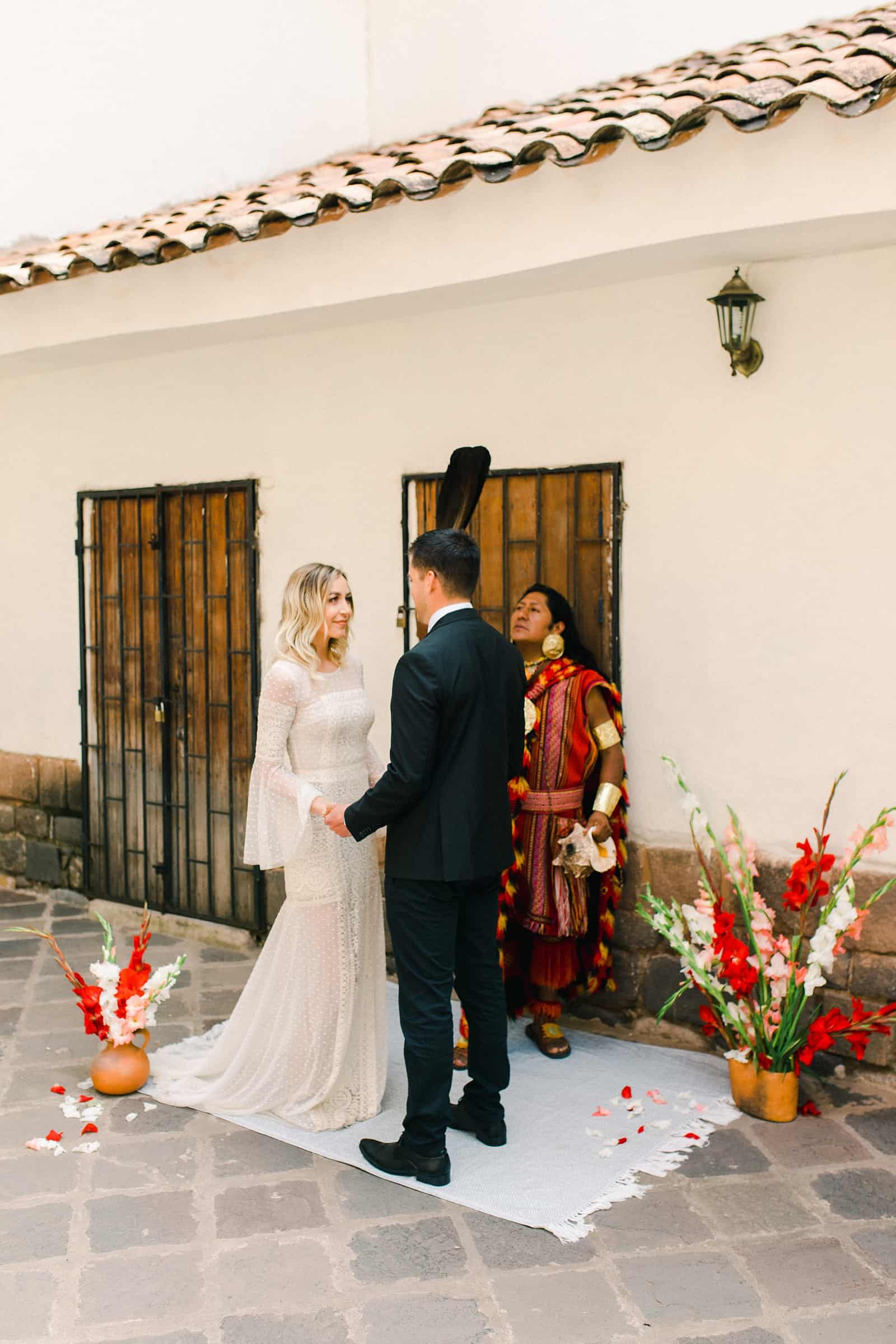 Cusco Peru Destination Wedding, travel wedding photography, Plaza de Armas ceremony with shaman, red flowers boho wedding