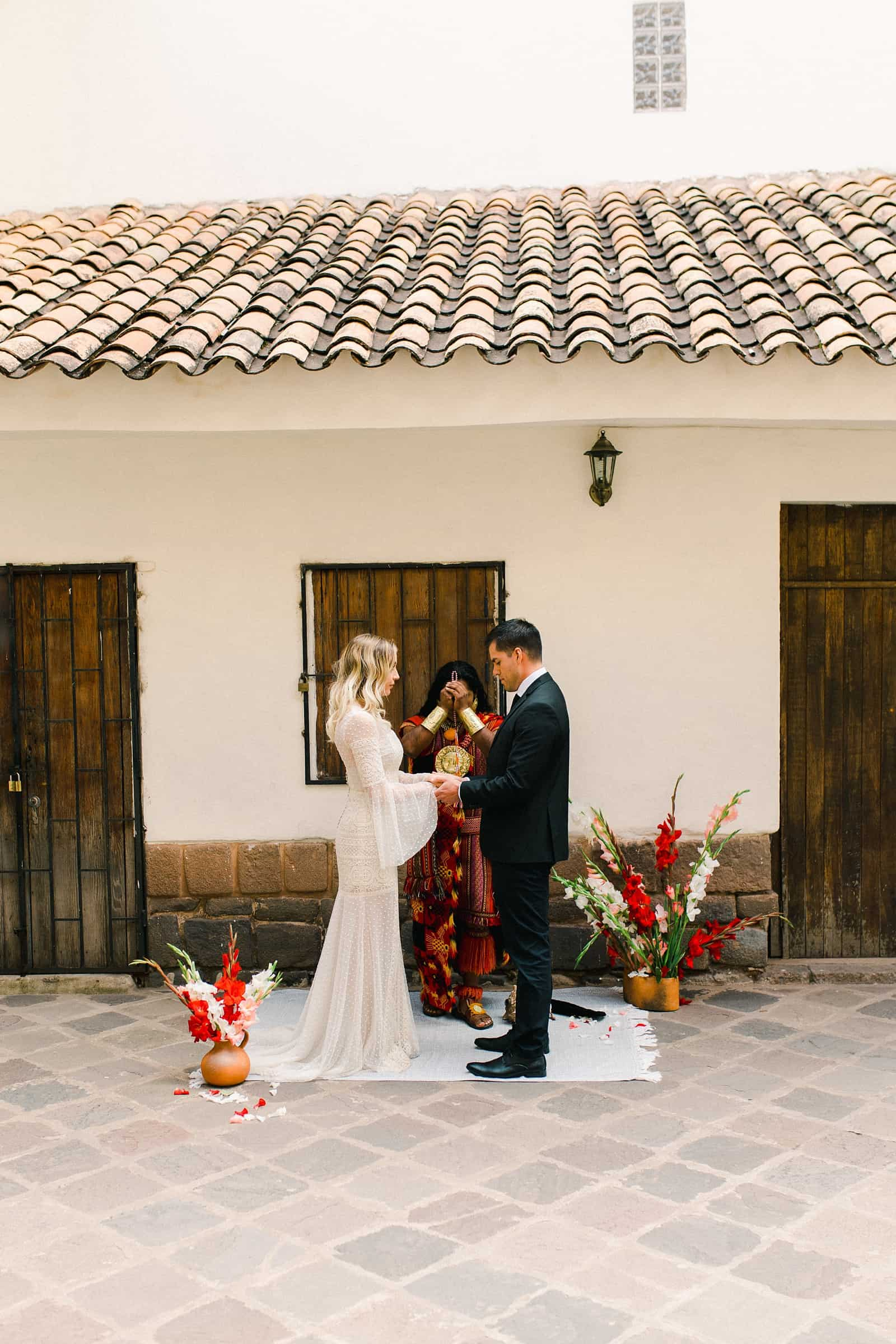 Cusco Peru Destination Wedding, travel wedding photography, Plaza de Armas ceremony with shaman, red flowers Spanish boho wedding