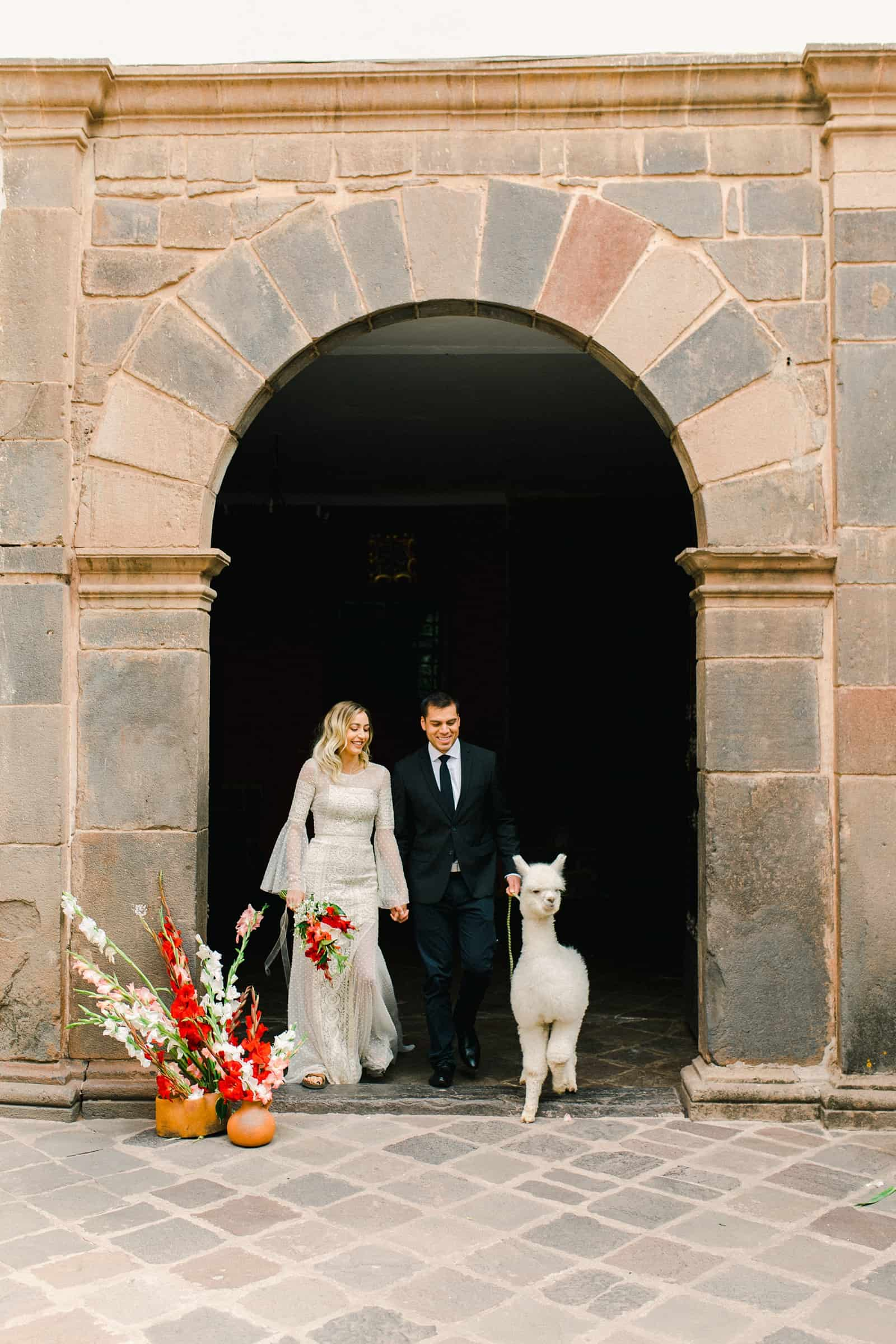 Cusco Peru Destination Wedding, travel wedding photography, Plaza de Armas red flowers boho wedding with white alpaca llama