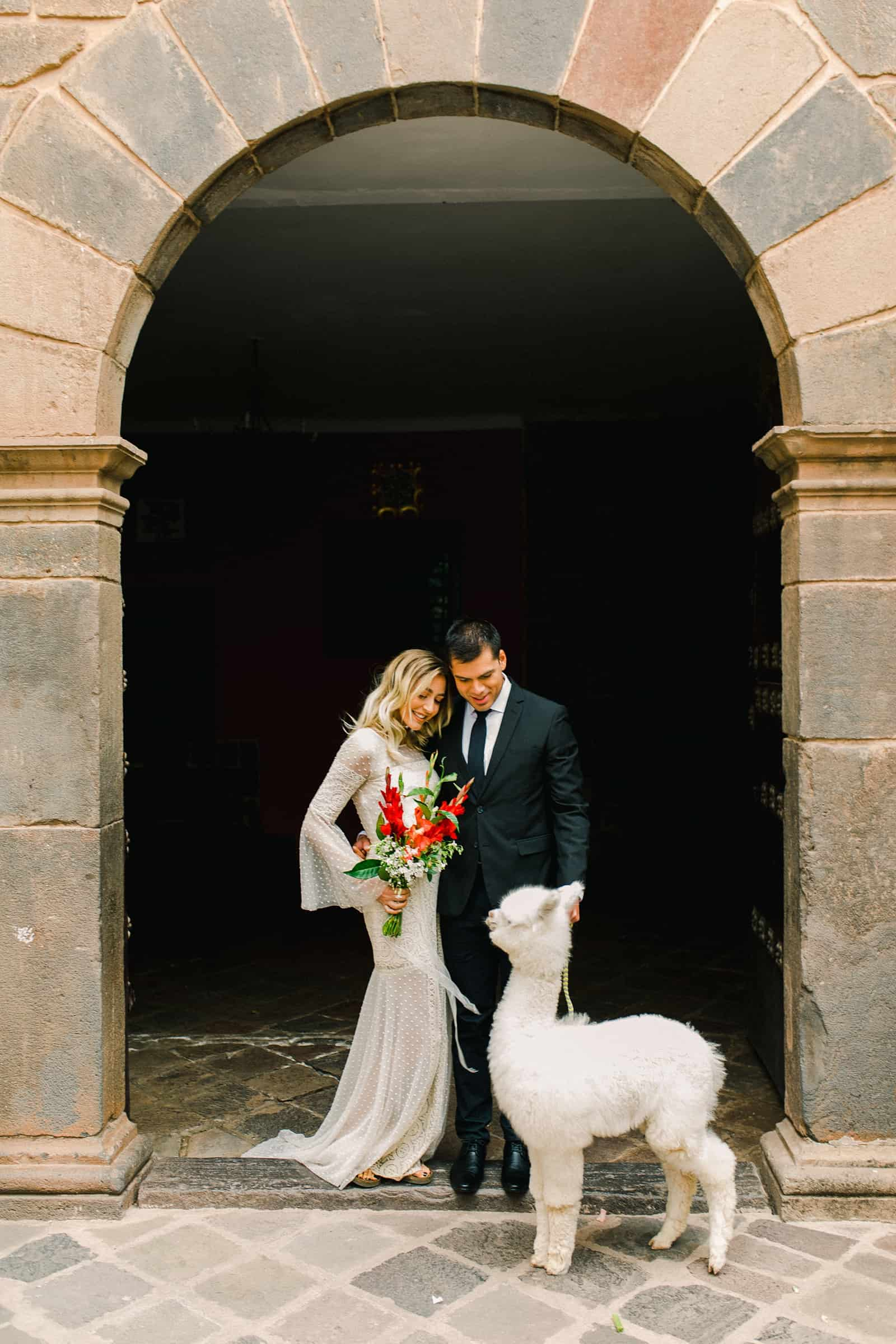 Cusco Peru Destination Wedding, travel wedding photography, Plaza de Armas red flowers boho wedding, bride and groom with white alpaca llama, red bouquet