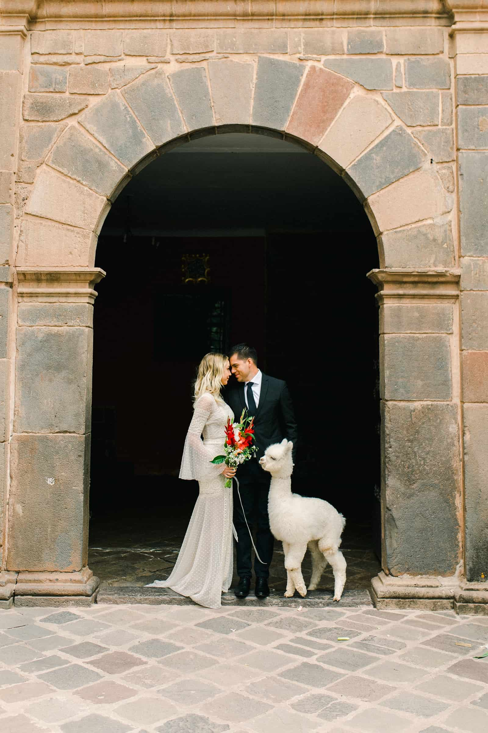Cusco Peru Destination Wedding, travel wedding photography, Plaza de Armas red flowers boho wedding, bride and groom with white alpaca llama