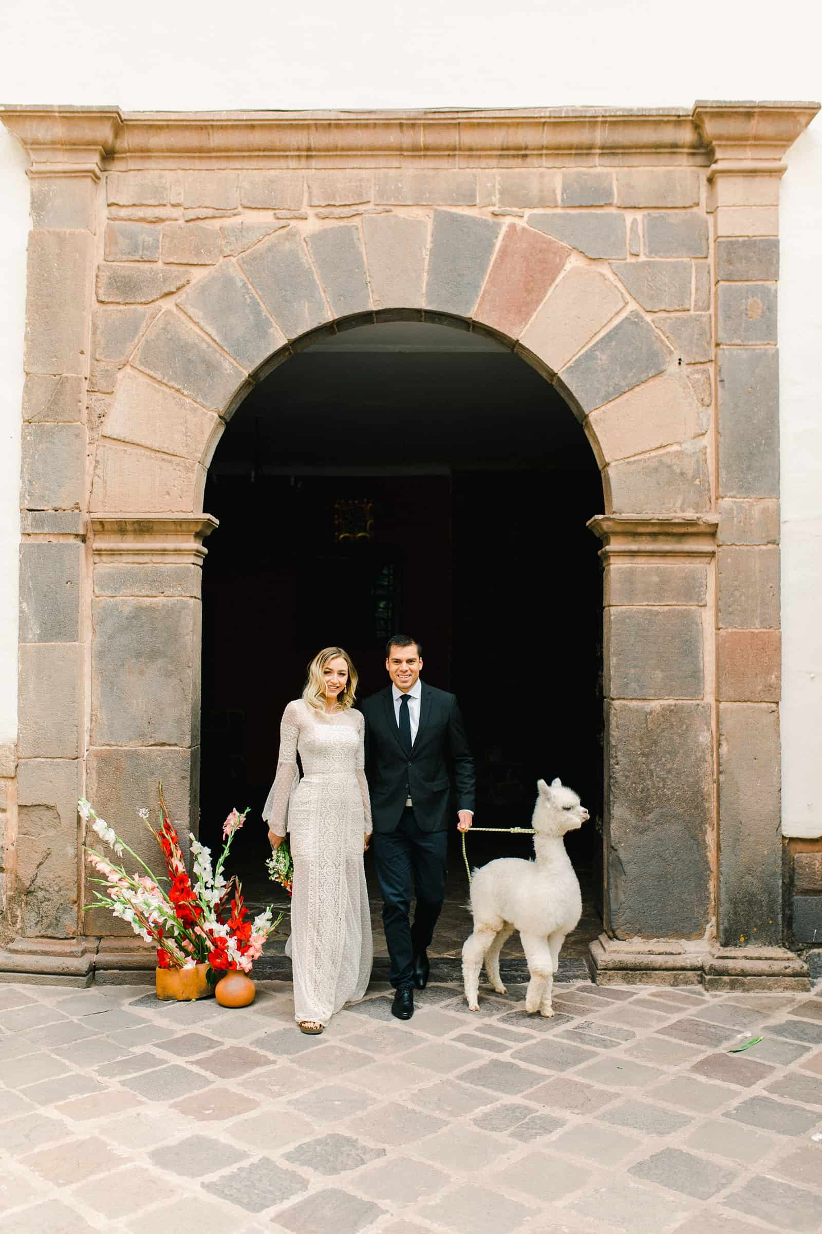 Cusco Peru Destination Wedding, travel wedding photography, Plaza de Armas red flowers boho wedding, bride and groom with white alpaca llama, red flowers bouquet