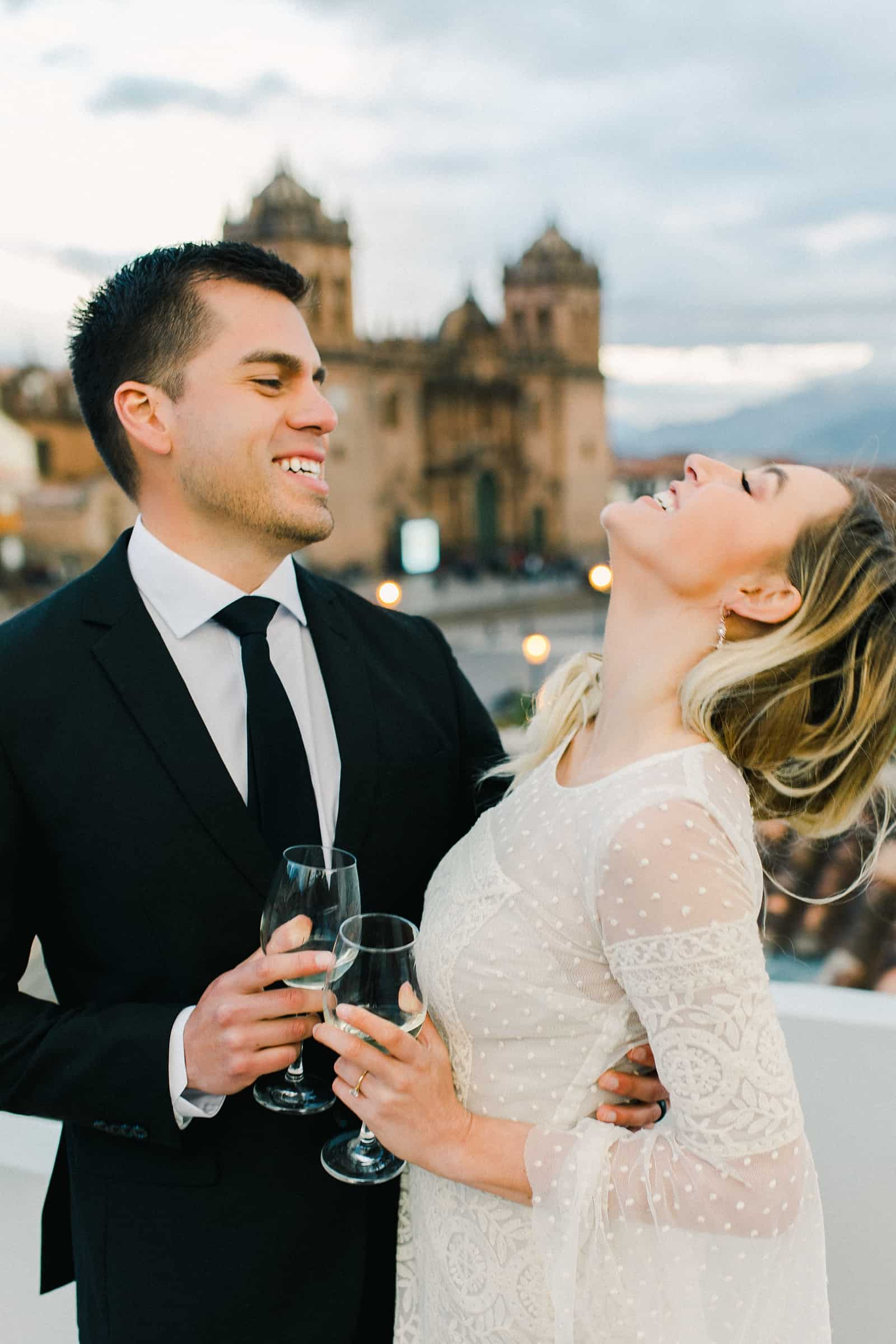 Cusco Peru Destination Wedding Inspiration, travel photography, bride and groom wedding dinner overlooking Cusco Cathedral , champagne toast
