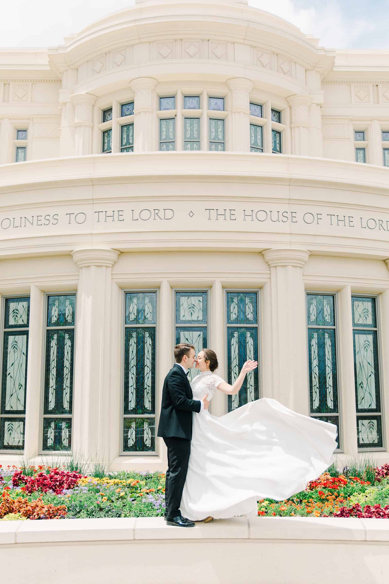 Payson Utah Temple wedding, bride and groom kiss near flower garden