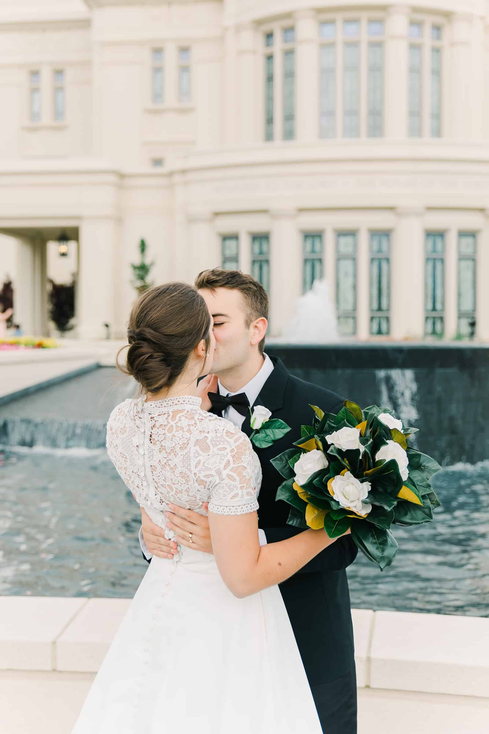 Payson Utah Temple wedding, bride and groom kiss, white rose bouquet with magnolia leaves