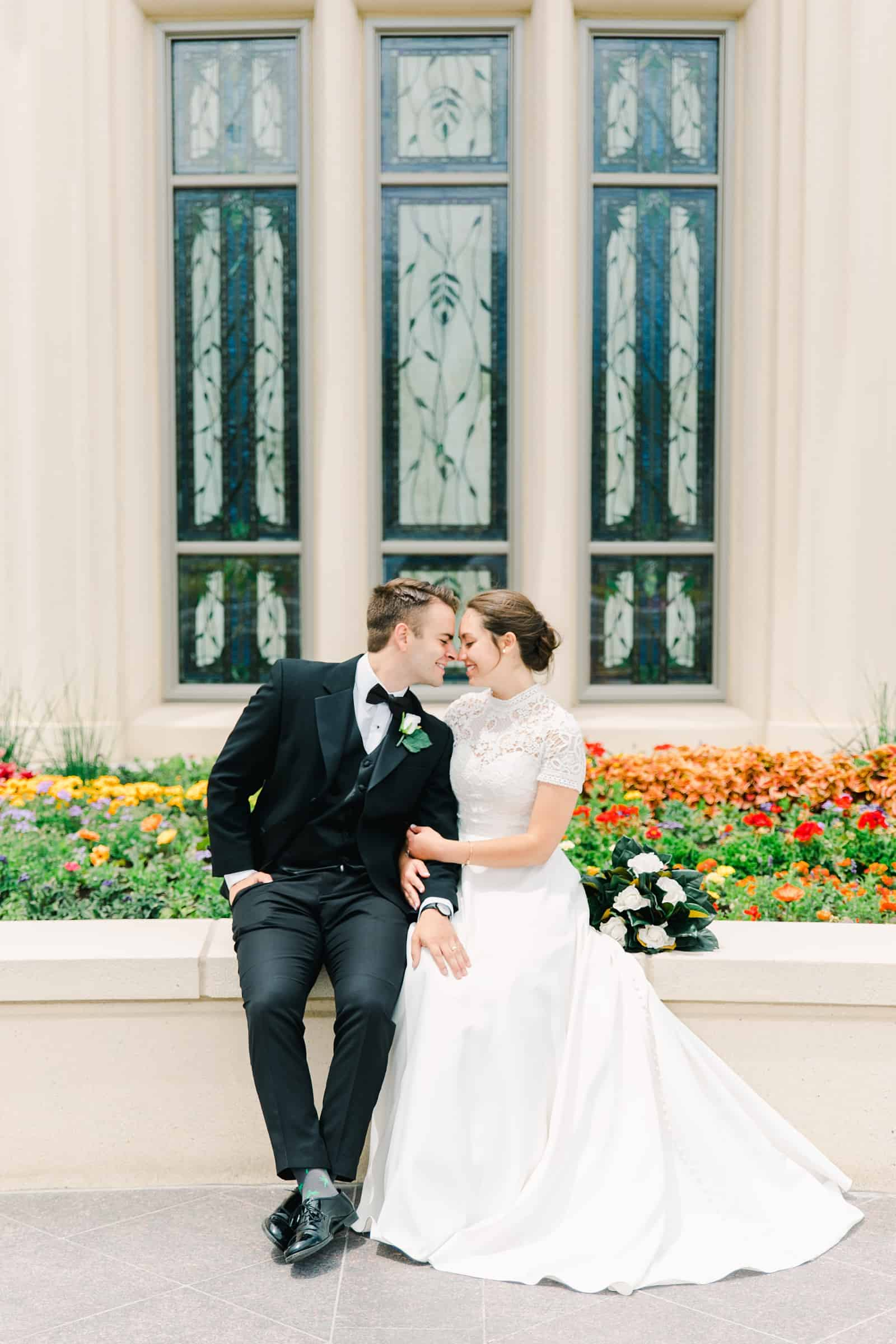 Payson Utah Temple wedding, bride and groom sit near flower garden