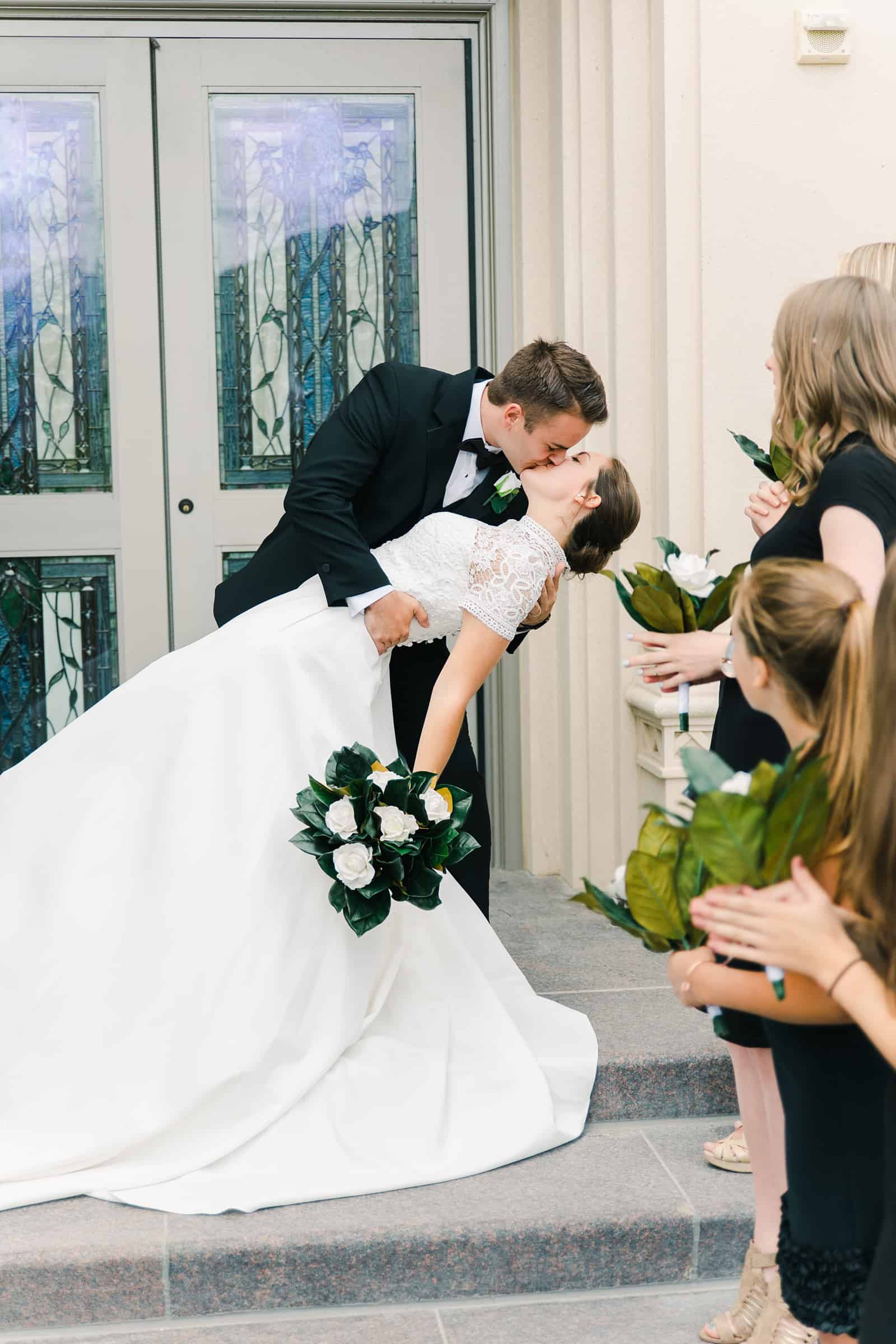 Payson Utah Temple wedding, bride and groom exit and dip kiss