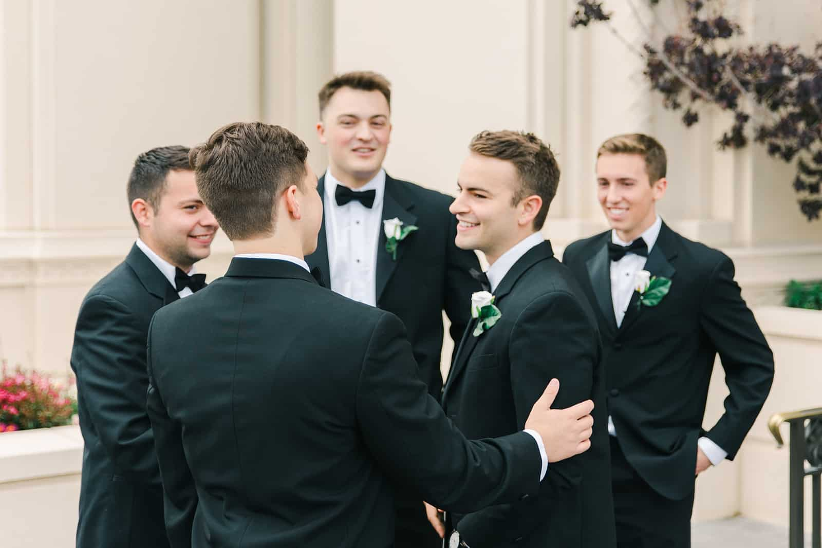 Payson Utah Temple wedding, groom with groomsmen wearing classic black tuxes with black bow ties