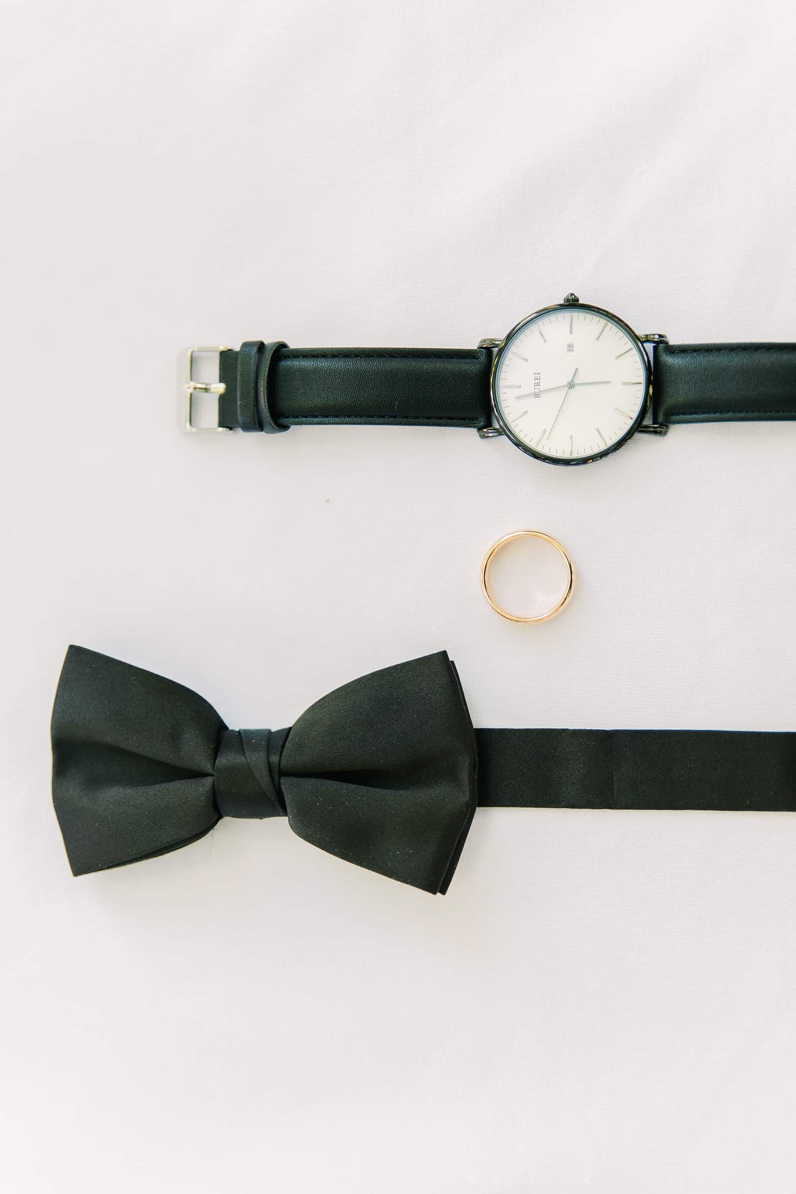 Classic black Utah wedding details, groom black bow tie and watch with gold wedding ring