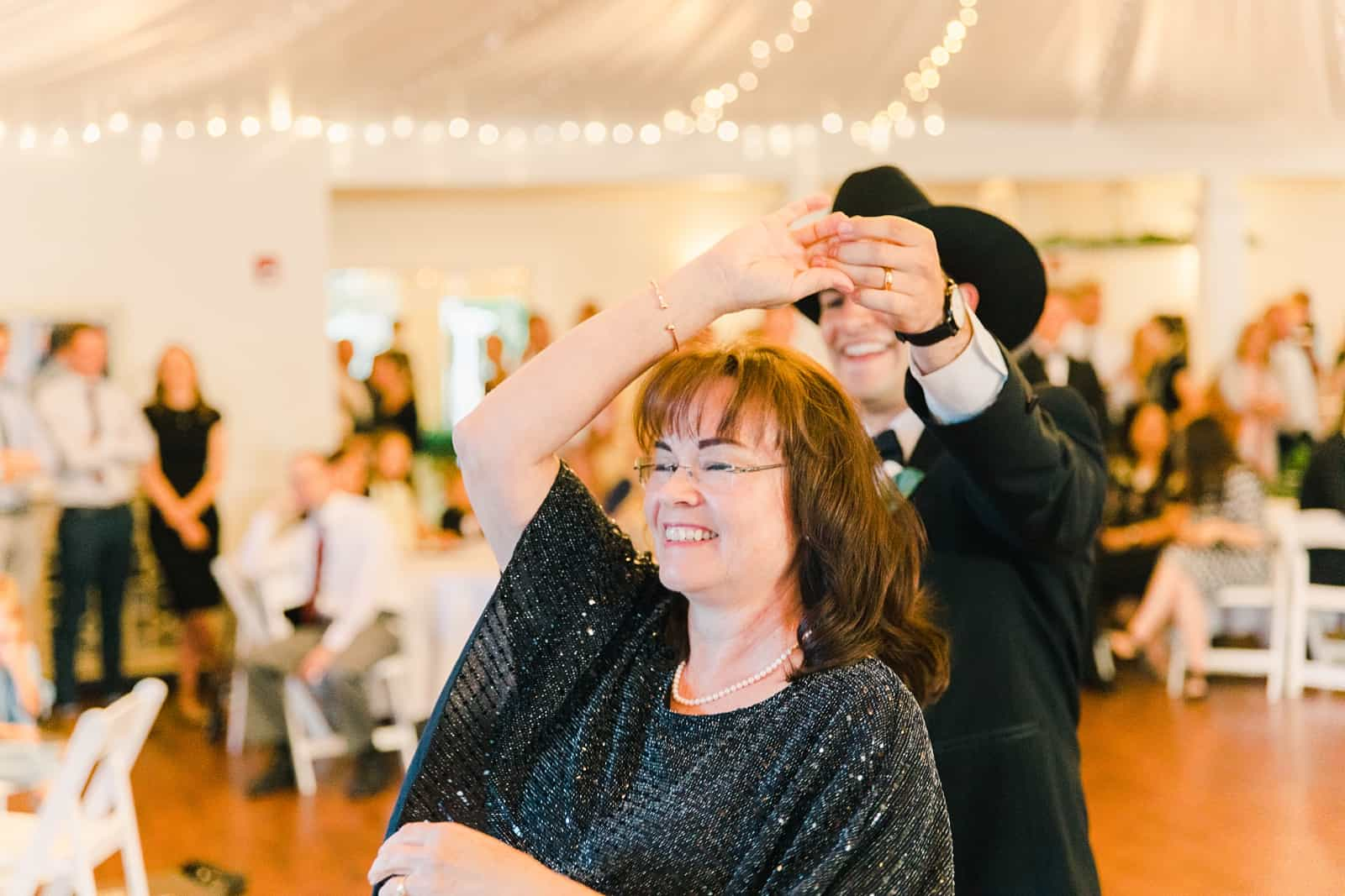 Clarion Gardens Payson Utah Wedding, groom wears cowboy hat and dances with mother of the groom