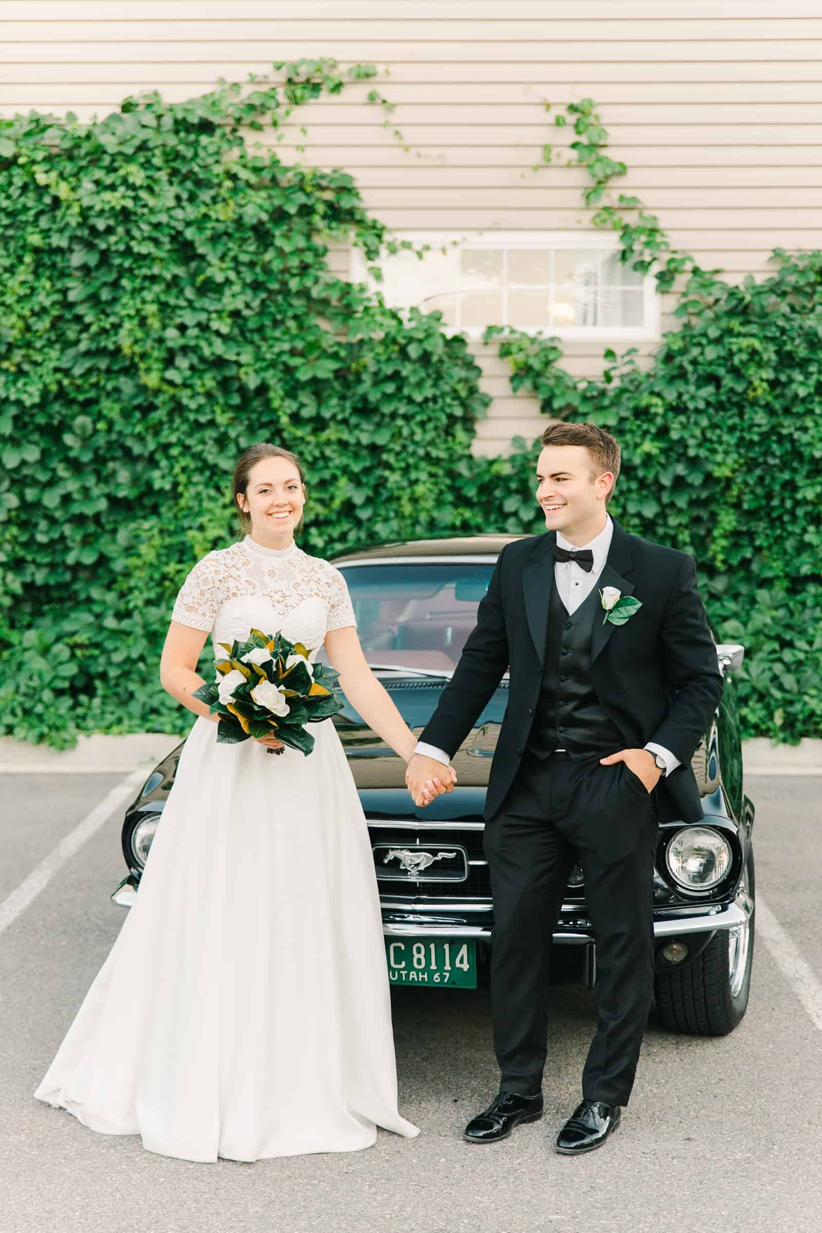 Clarion Gardens Payson Utah Wedding, bride and groom pose with black vintage Mustang convertible, ivy wall background