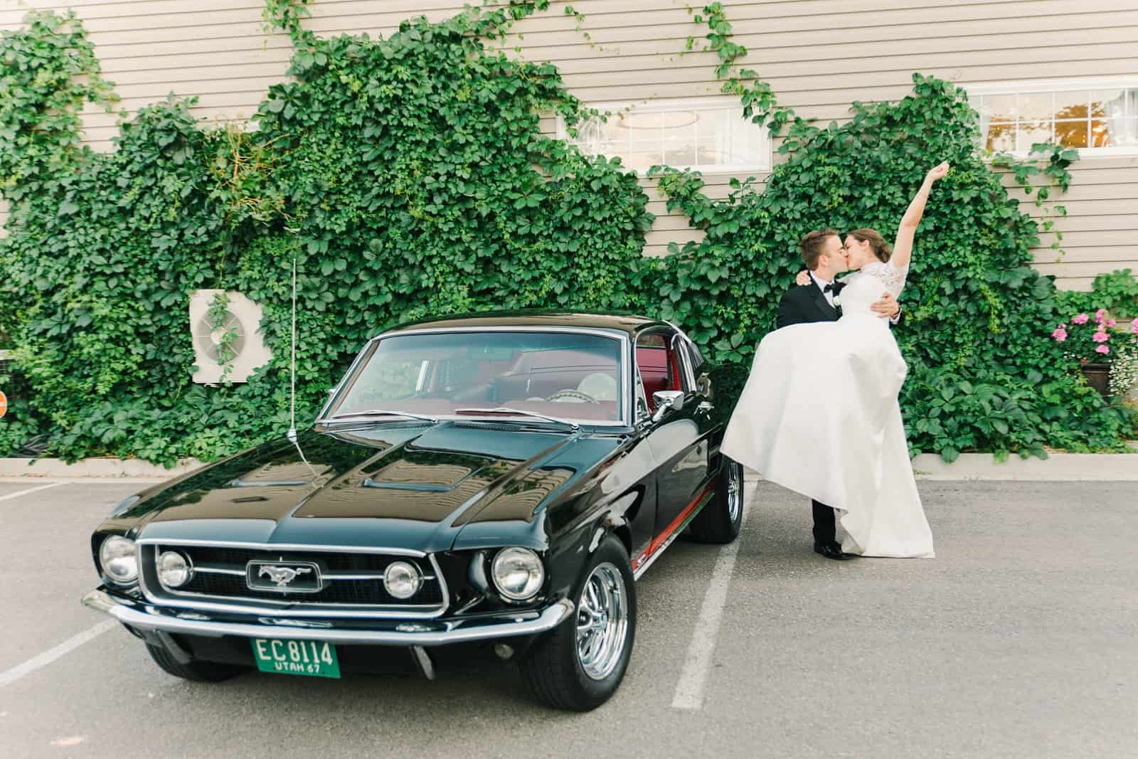 Clarion Gardens Payson Utah Wedding, bride and groom pose with black vintage Mustang convertible reception getaway car