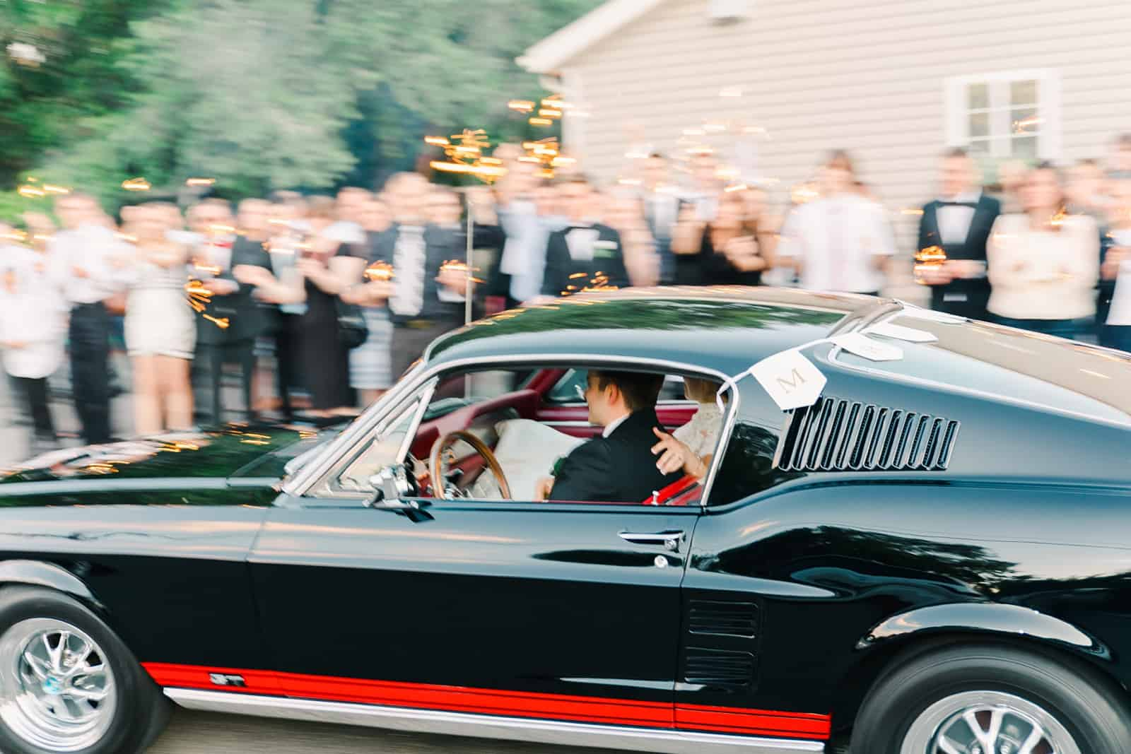Clarion Gardens Payson Utah Wedding, bride and groom drive away in black vintage Mustang convertible reception getaway car