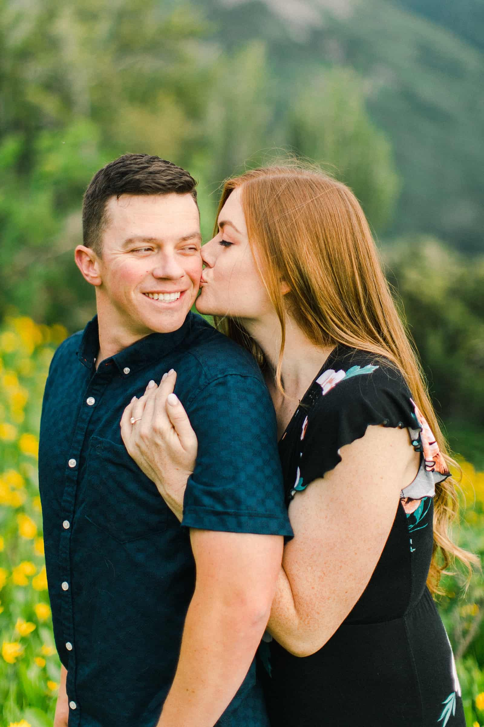 Provo Canyon wildflowers field engagement session, Utah wedding photography, engaged couple kissing in yellow flowers and mountains