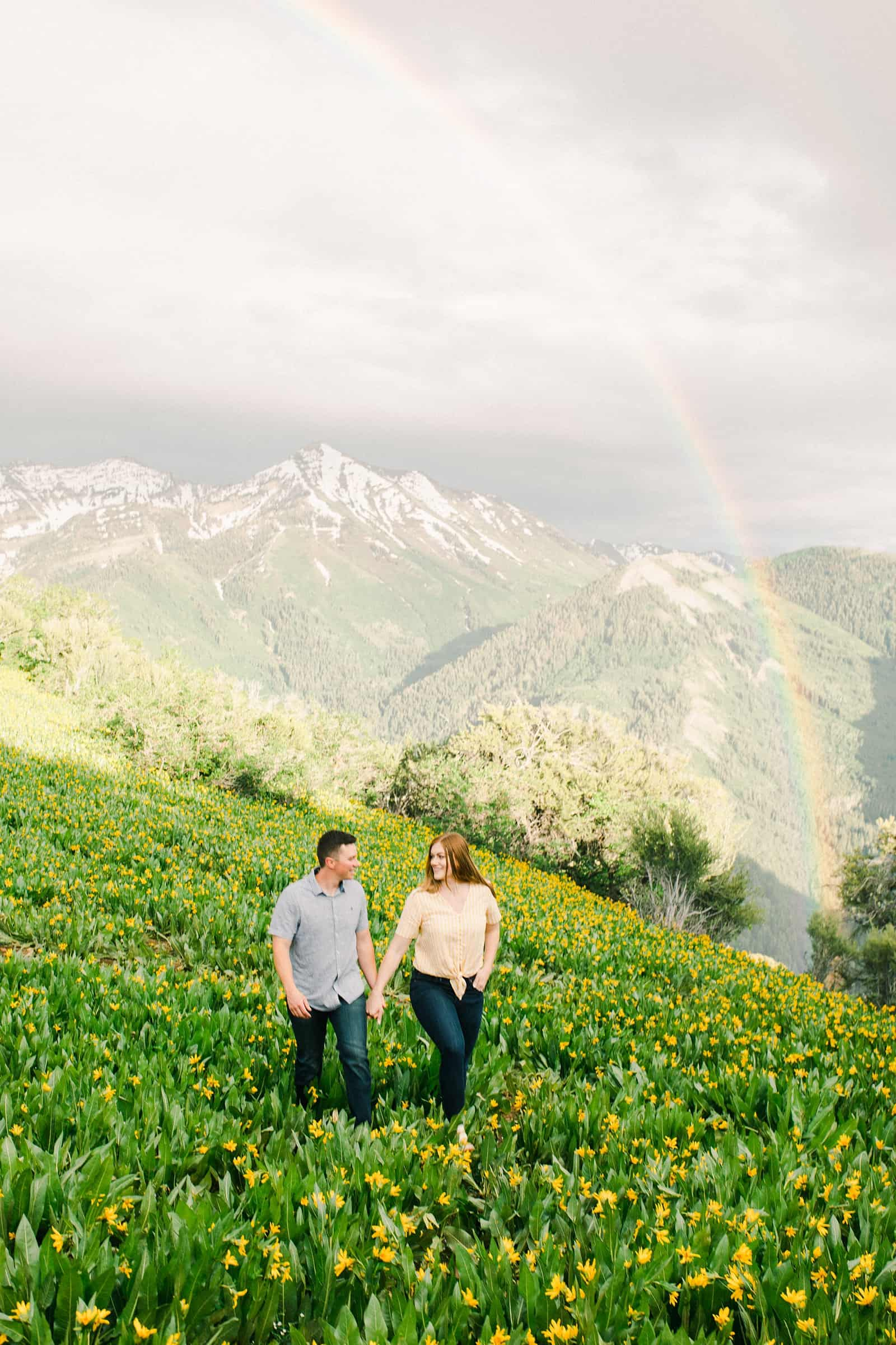 Provo Canyon wildflowers field engagement session, Utah wedding photography, engaged couple walking in yellow flowers and mountains with rainbow in background