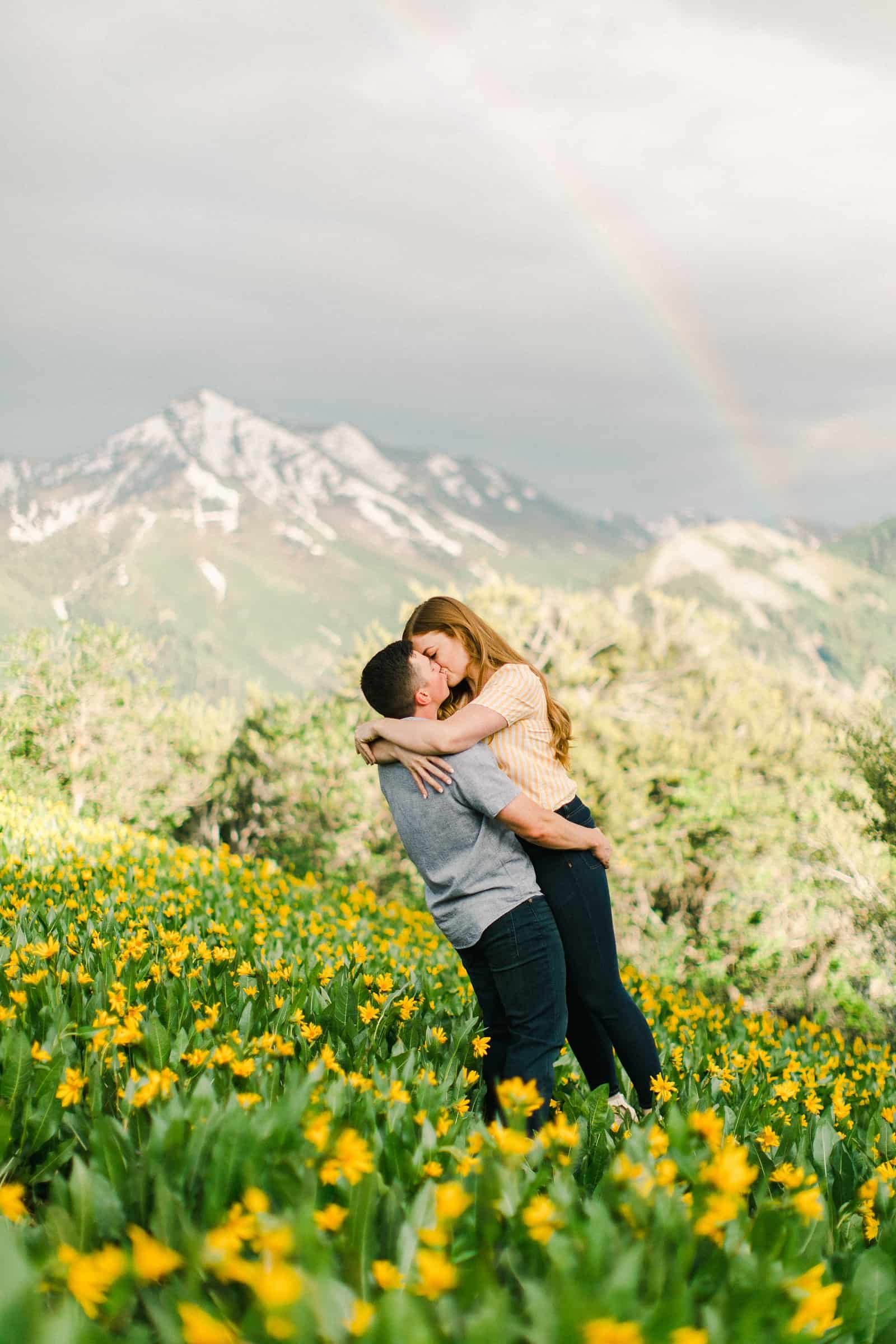 Provo Canyon wildflowers field engagement session, Utah wedding photography, engaged couple kissing in yellow flowers and mountains with rainbow in background