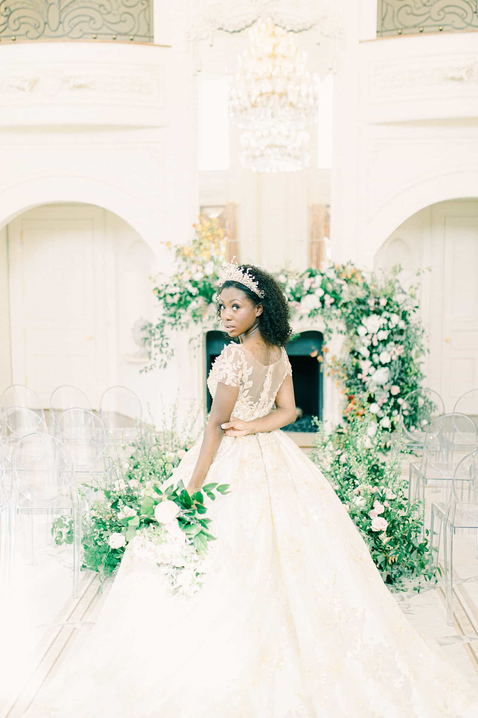 Disney princess bride with tiara in front of greenery and floral arch, garland ceremony decor