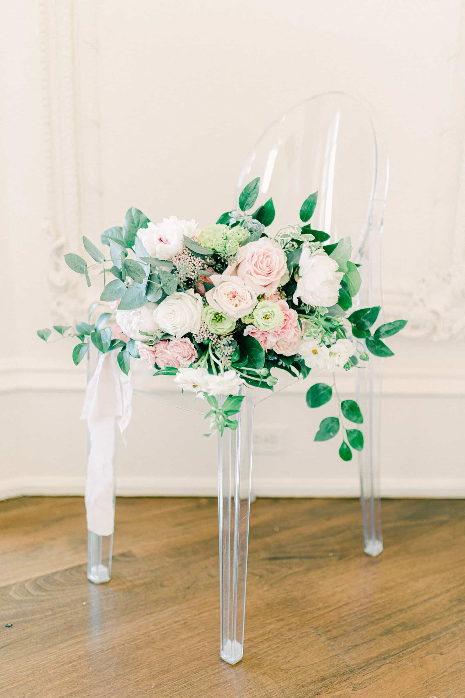 Wedding bouquet with white, green and pink flowers and eucalyptus on clear ghost chair