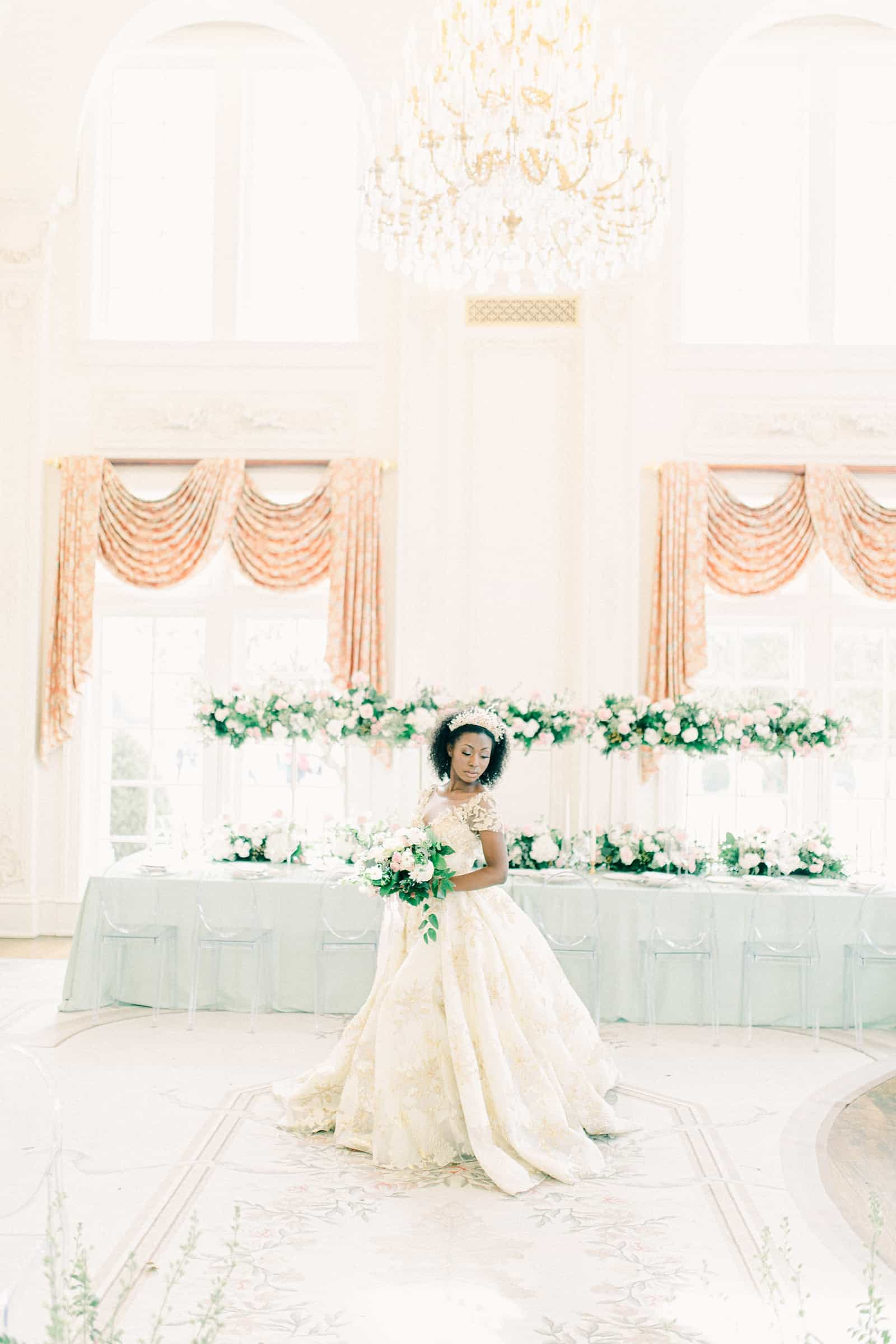 Bride wearing lace ball gown in front of long dining table with light blue tablecloth and tall canopy centerpieces