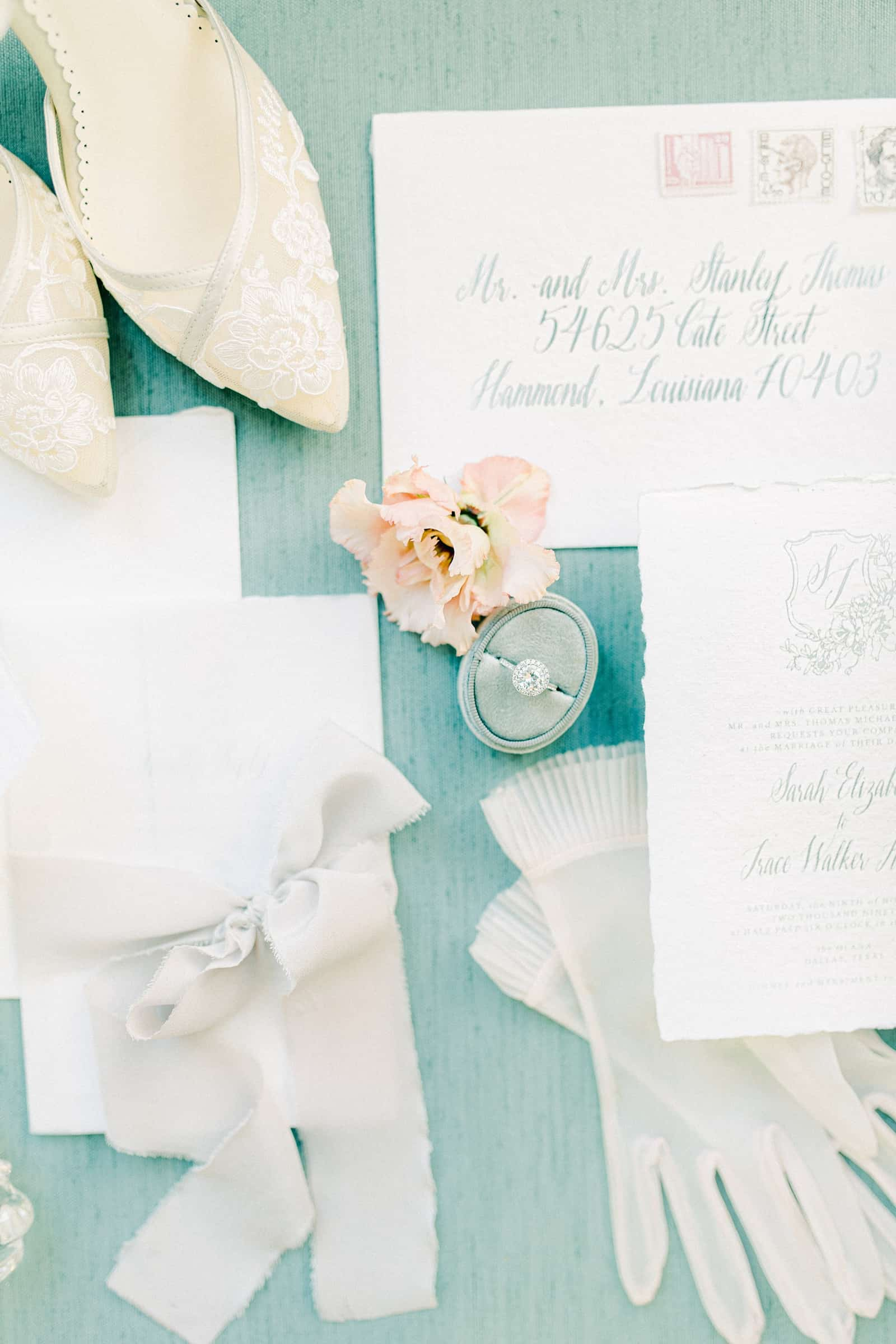 Oval velvet ring box with round cushion cut diamond wedding engagement ring, fine art sketched European style wedding invitations on light blue background
