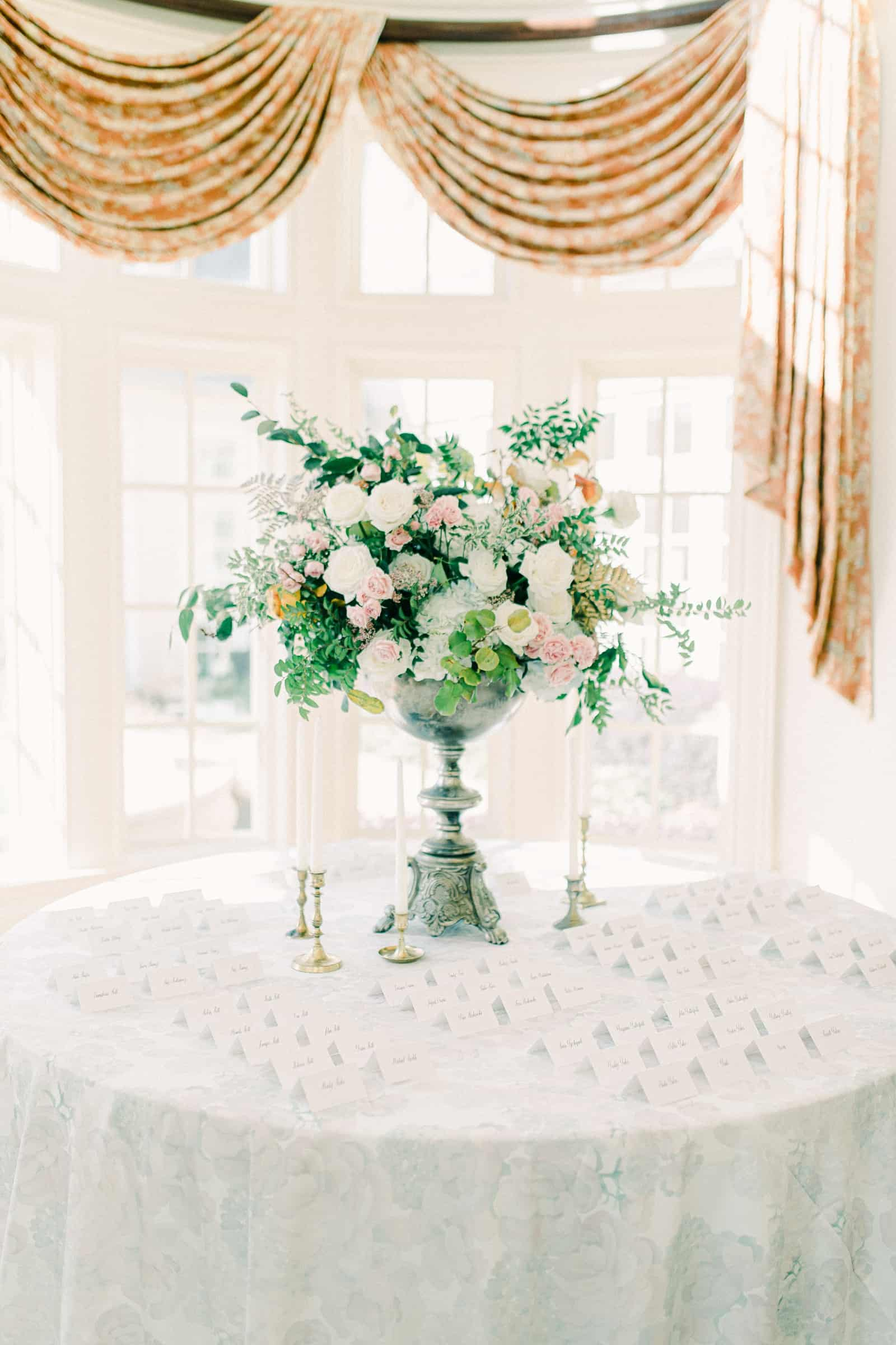 Tall wedding centerpiece with pink and white flowers, calligraphy place cards on light blue tablecloth