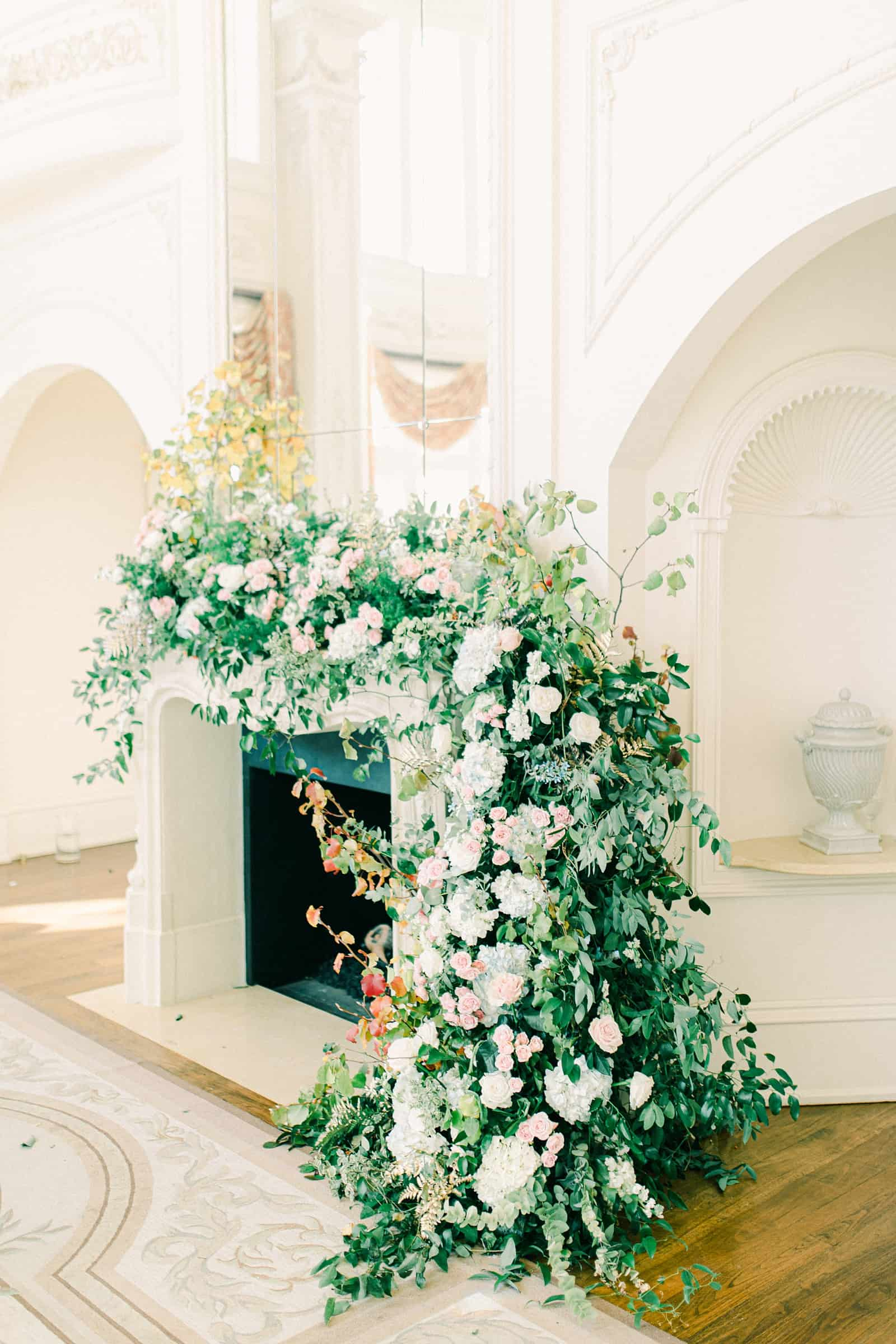 Ceremony backdrop garland with greenery and flowers in front of fireplace