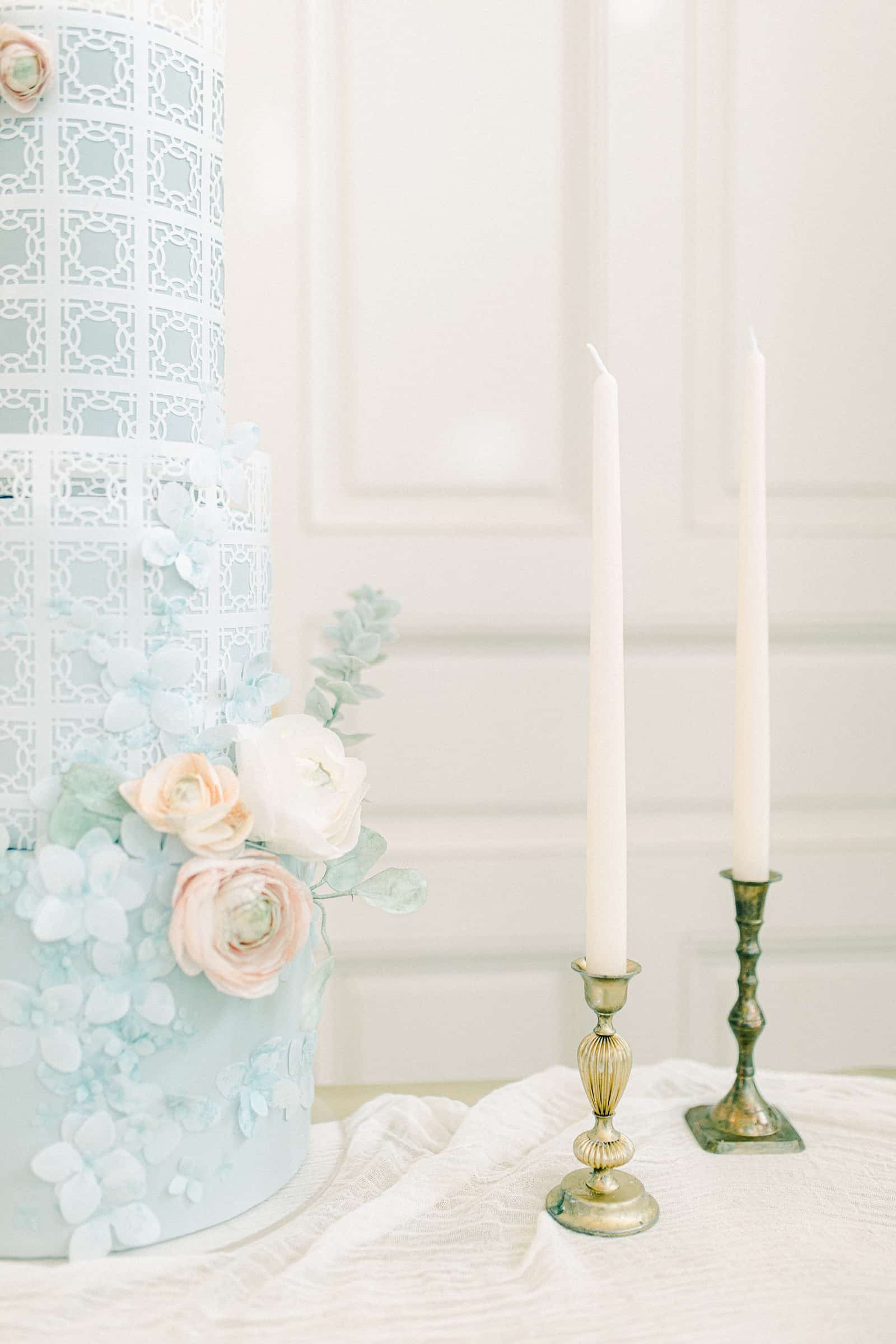 Light blue wedding cake with pink and white sugar flowers with gold candlesticks