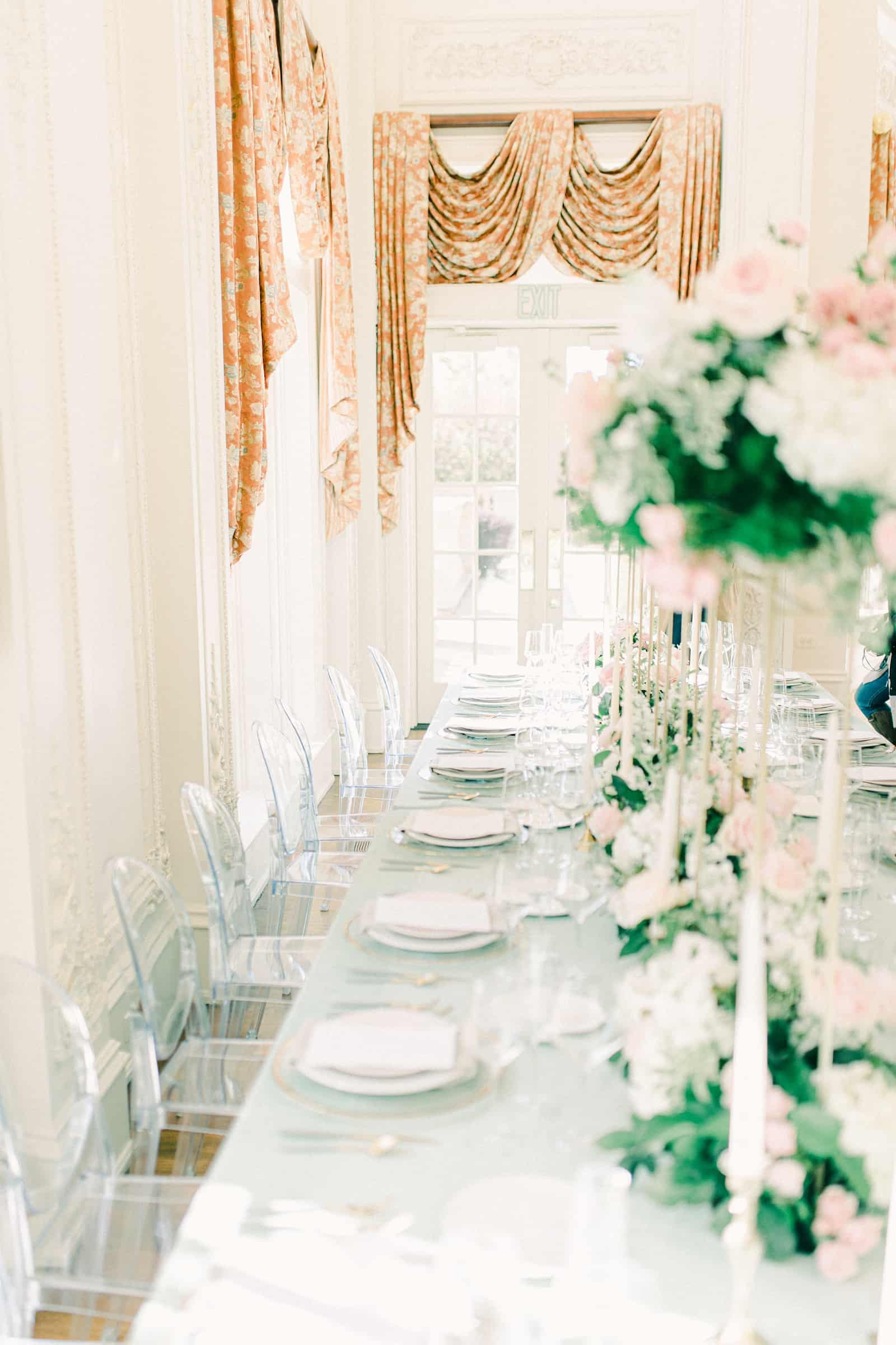Long wedding dining table with light blue tablecloth, clear dining chairs, tall pink and white flower centerpieces